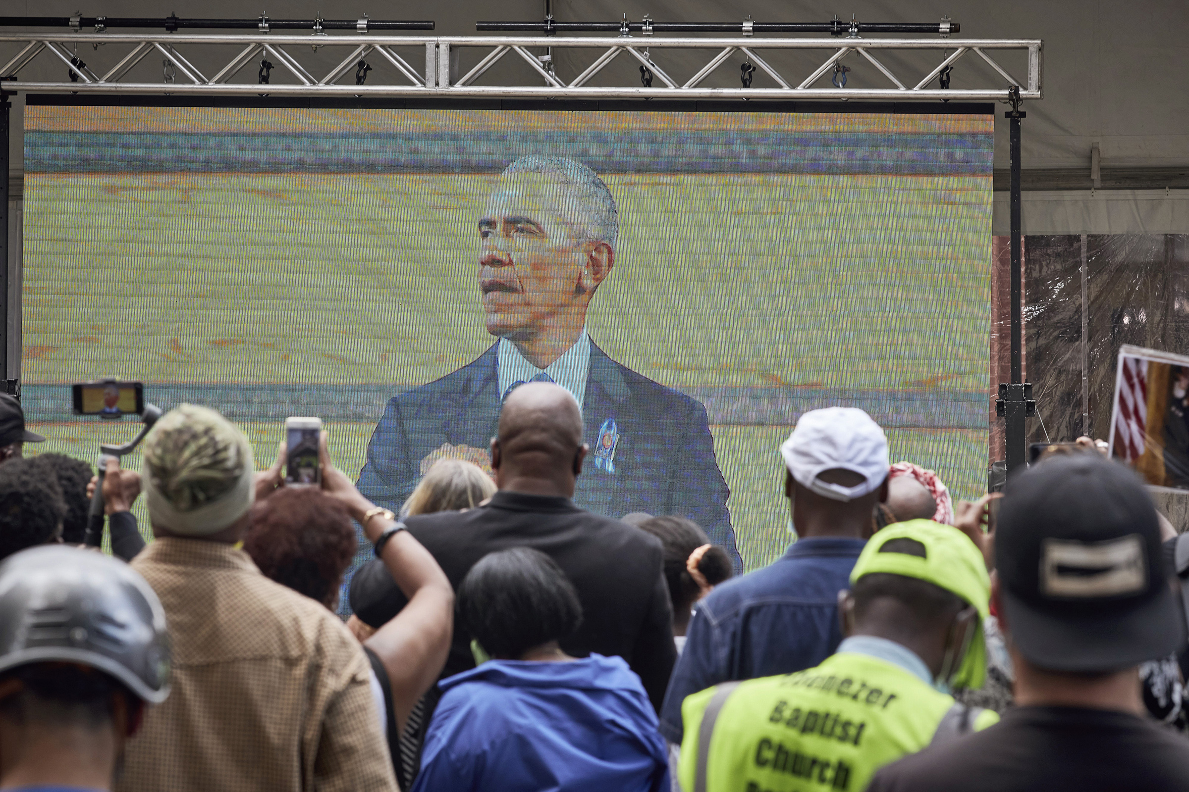 Mourners watch a broadcast of former President Barack Obama speaking at the funeral for the late Rep. John Lewis (D-Ga.) outside Ebenezer Baptist Church, where Lewis' funeral is taking place, in Atlanta, July 30, 2020.