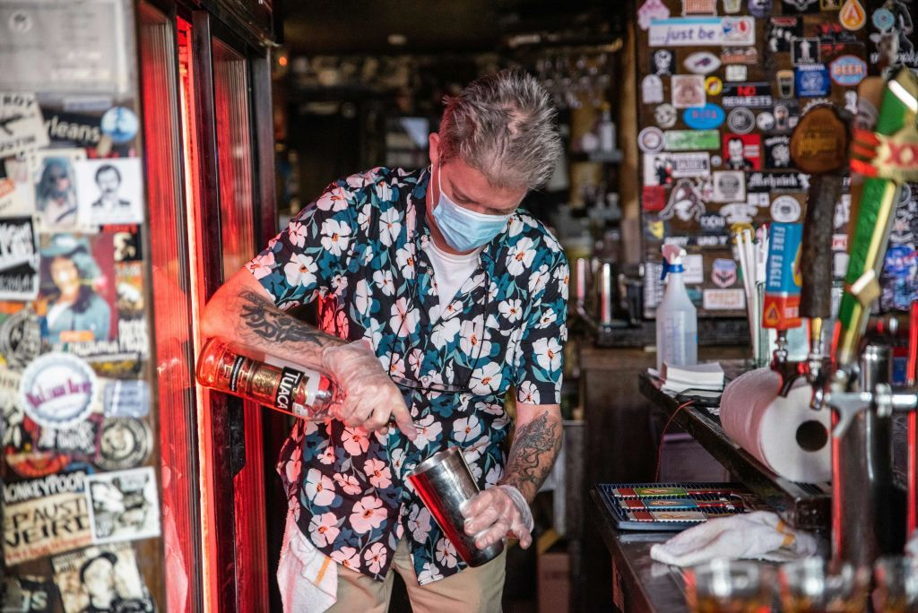 A bartender wearing a facemask makes a drink at a restaurant in Austin, Texas, June 26, 2020.