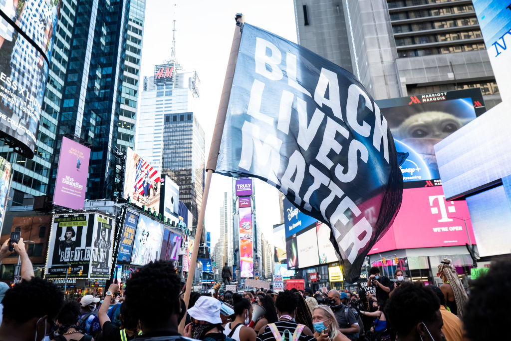 A protester holds a large flag that says,  Black Lives Matter  during a peaceful protest in New York City's Times Square on July 26, 2020.