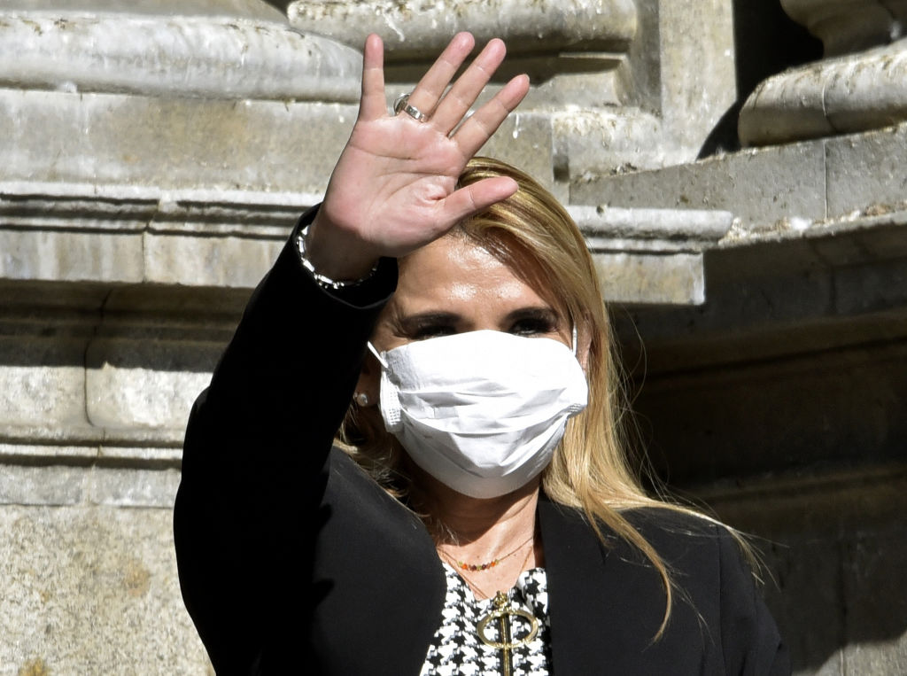 Bolivian interim President Jeanine Anez waves, while wearing a face mask, after attending a Corpus Christi procession at the Plaza de Armas in front of the government palace in La Paz, on June 11, 2020, amid the COVID-19 coronavirus pandemic.