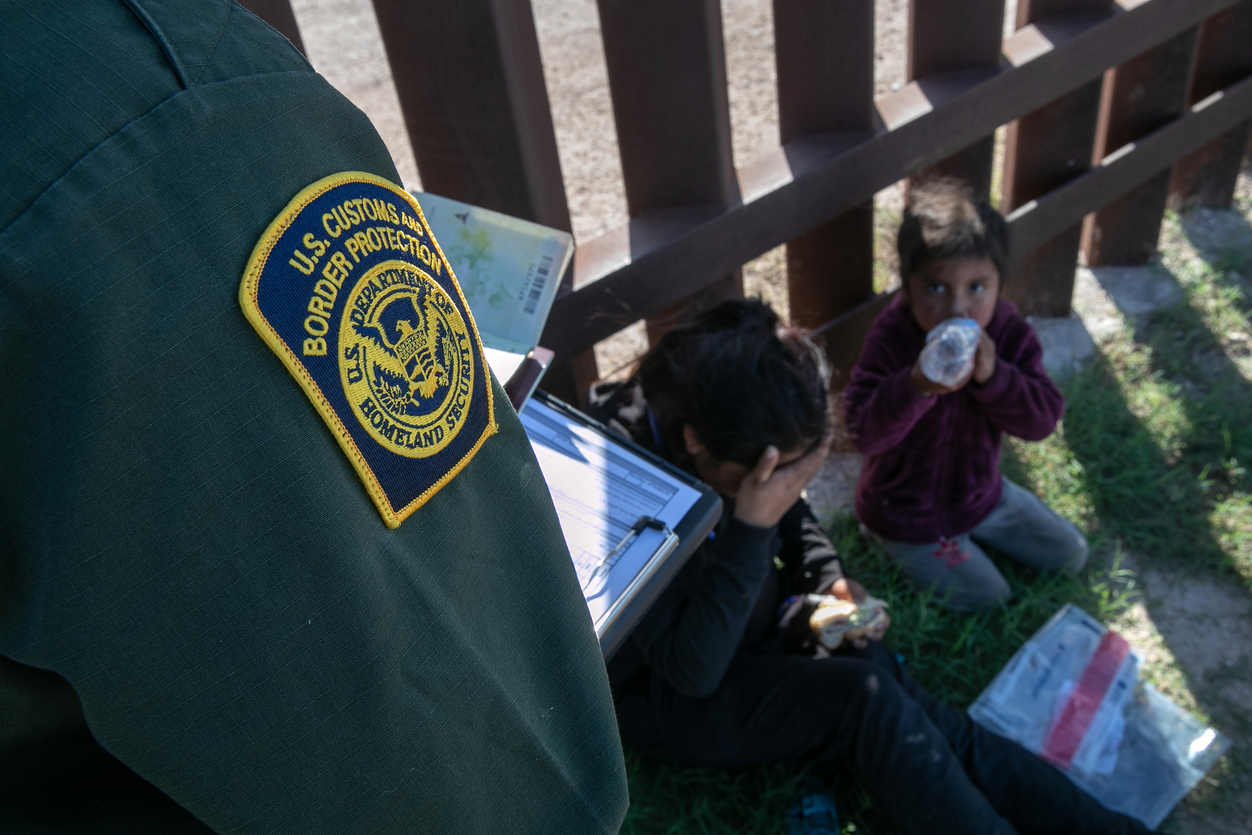 A U.S. Border Patrol agent checks the passports of a mother and daughter from Ecuador next to the border fence, after detaining them on Sept. 10, 2019 in Penitas, Texas.