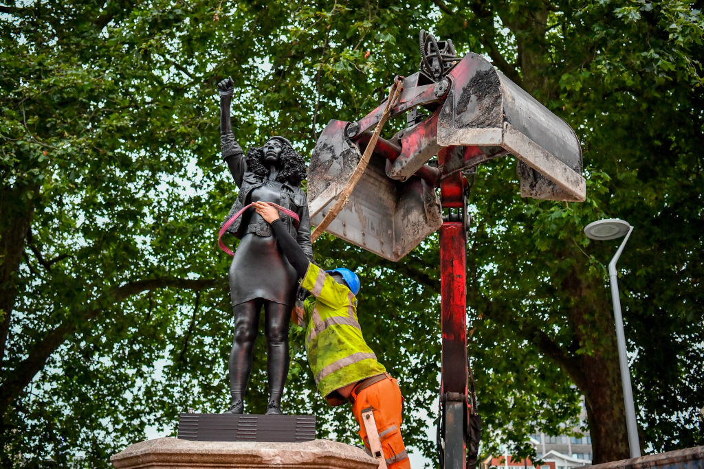 Contractors use ropes to secure A Surge of Power (Jen Reid) 2020, by prominent British sculptor Marc Quinn, which has been installed in Bristol on the site of the fallen statue of the slave trader Edward Colston, as they prepare to remove and load it into into a recycling and skip hire lorry.