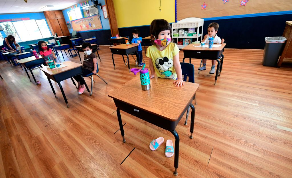 Children in a pre-school class wear masks and sit at desks spaced apart as per coronavirus guidelines during summer school sessions in Monterey Park, California on July 9, 2020.