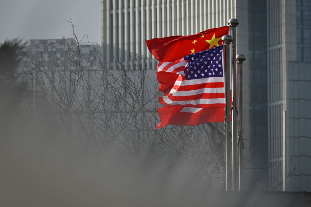 Chinese and U.S. flags are seen at the entrance of an office building in Beijing on Jan. 19, 2020.