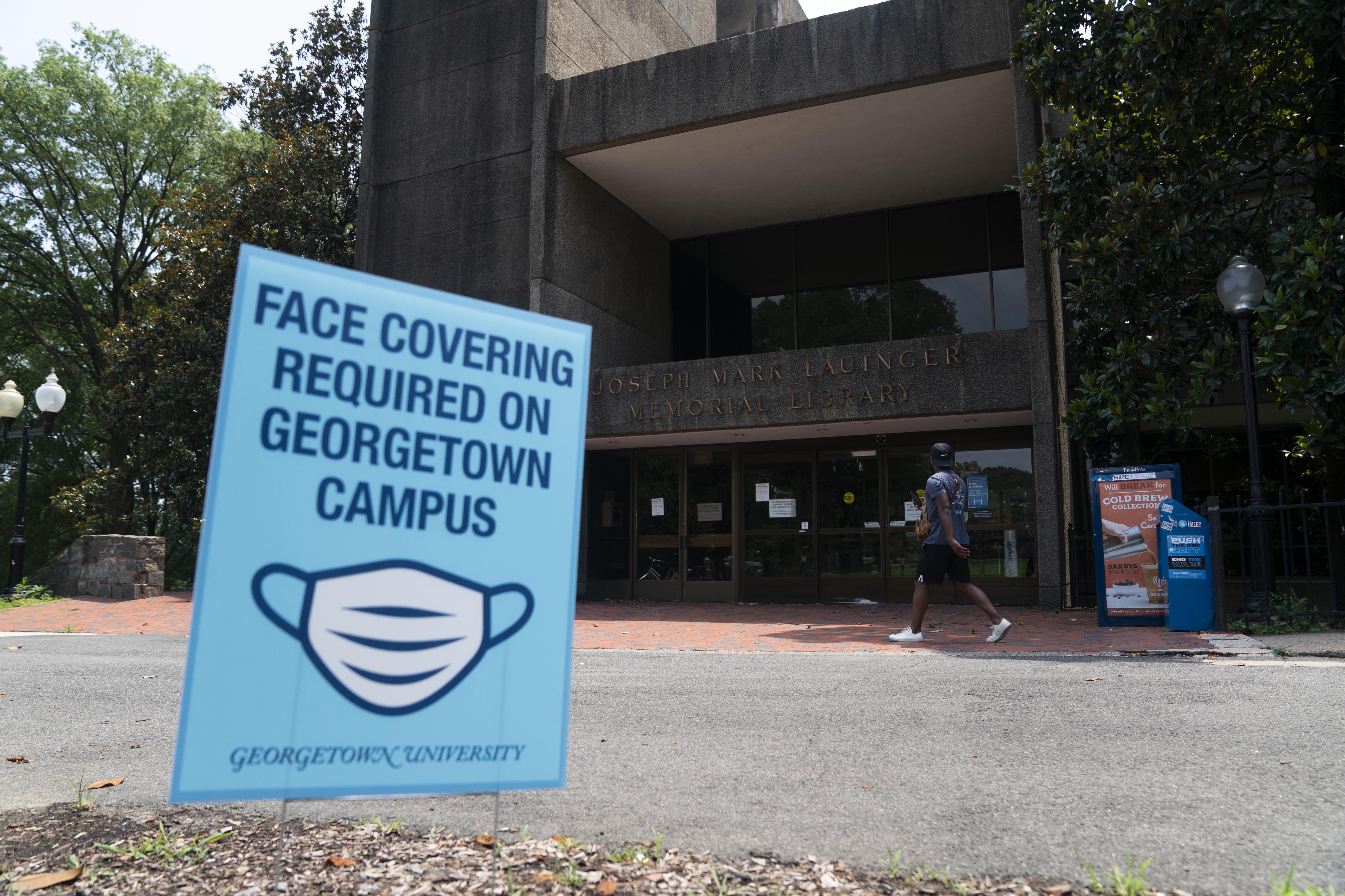 A sign reminding people to wear face masks is seen in front of a library on Georgetown University's main campus in Washington, D.C., on July 7, 2020.