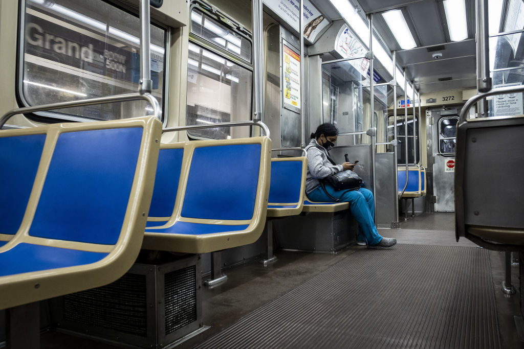 A commuter wearing a protective mask looks at a mobile device while riding a Chicago Transit Authority (CTA) train in Chicago, Illinois, U.S., on Wednesday, June 3, 2020.