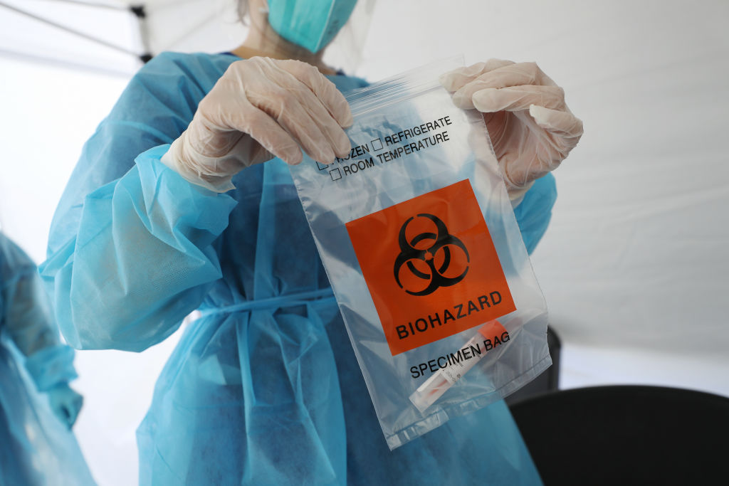 A nurse seals a specimen bag containing a COVID-19 test swab at a St. John's Well Child & Family Center mobile clinic set up outside Walker Temple AME Church in South Los Angeles amid the coronavirus pandemic on July 15, 2020 in Los Angeles, California.