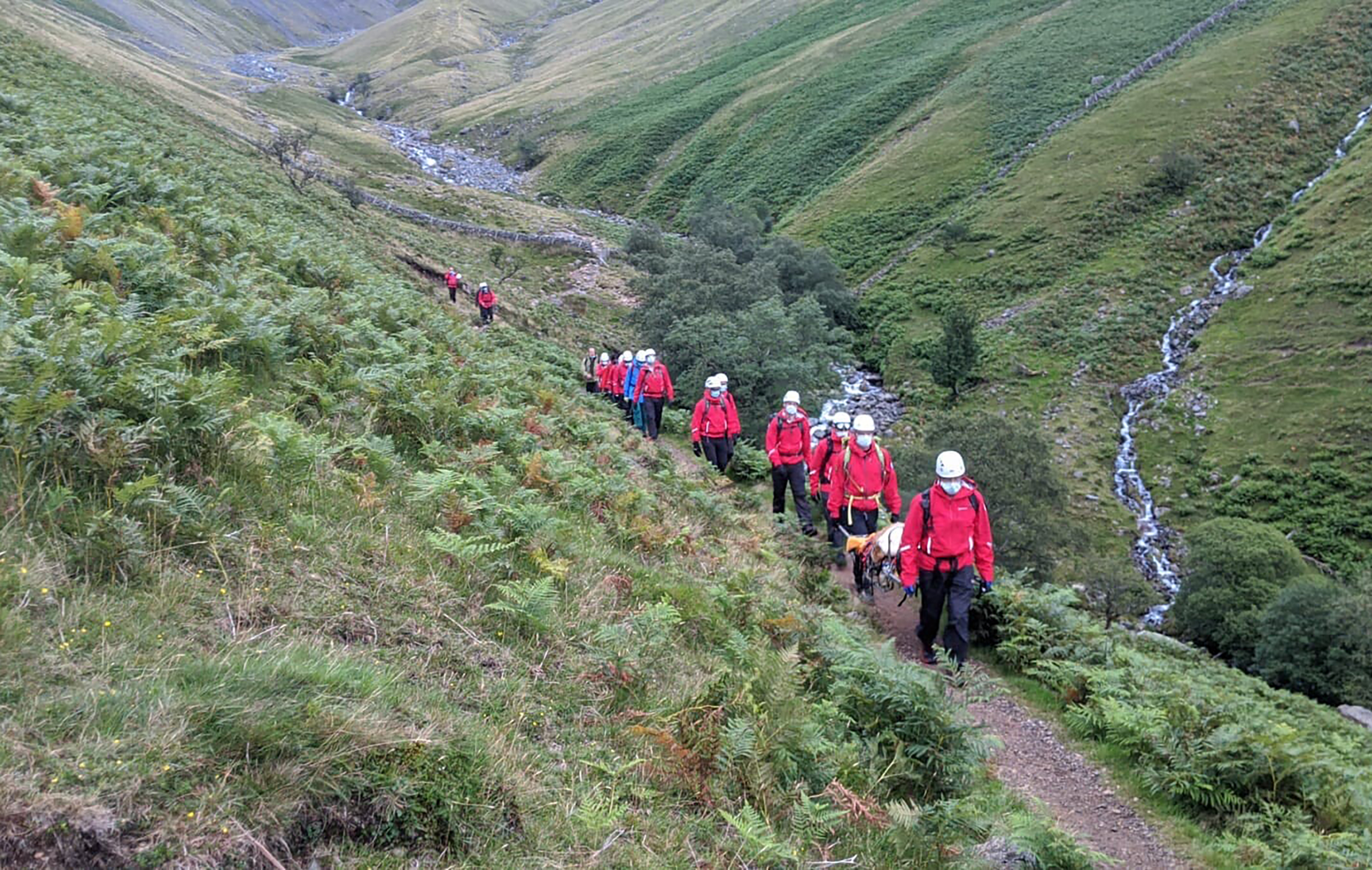 Volunteers from Wasdale mountain rescue team take turns to carry Diasy, a 121lb (55kg) St Bernard dog, from England's highest peak, Scafell Pike, on July 26, 2020.