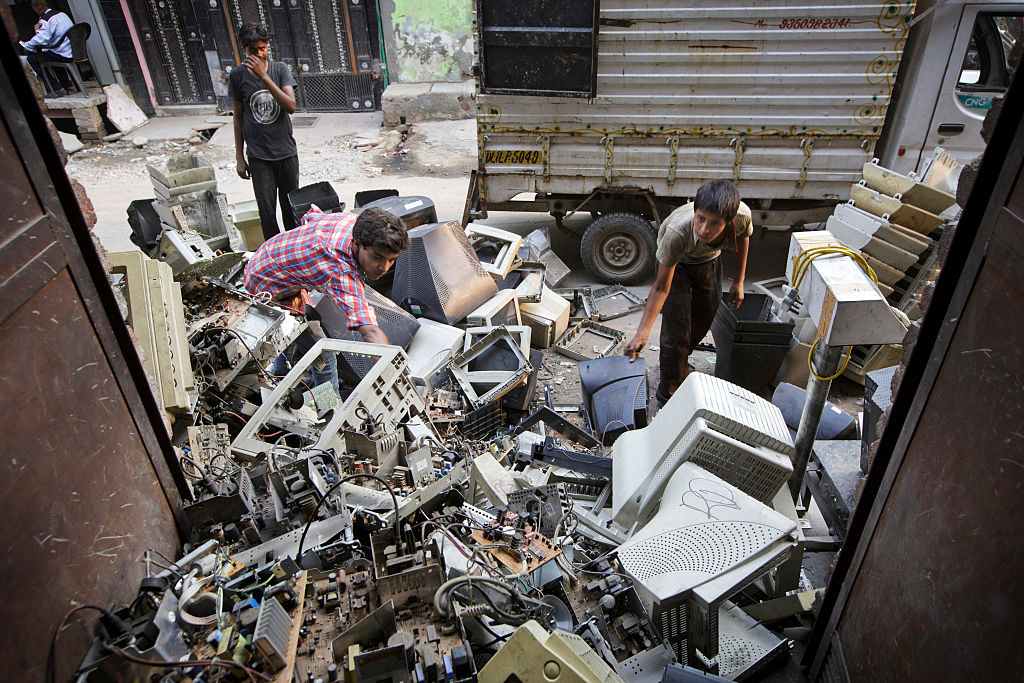 Workers sort through used computers and other electronic waste at a workshop in New Delhi, India.
