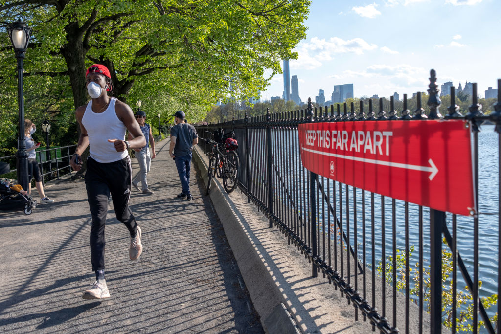 A man wearing a mask runs near a sign that says,  Keep this far apart  in Central Park in New York City on May 3, 2020.