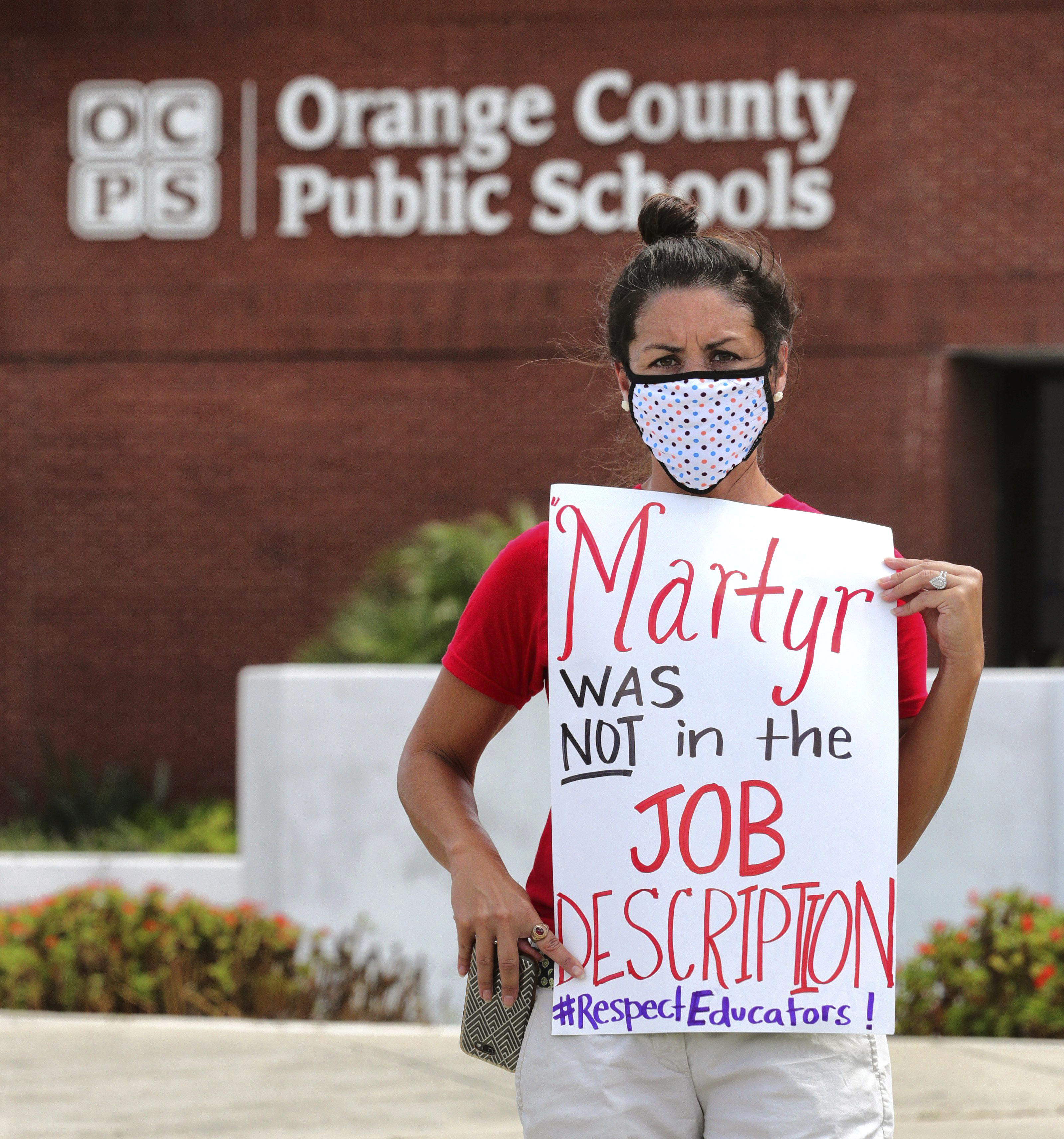 Rachel Bardes holds a sign in front of the Orange County Public Schools headquarters in Orlando, Fla., on July 7, 2020, as teachers protest a mandate that all public schools open in August despite the spike in coronavirus cases in Florida.