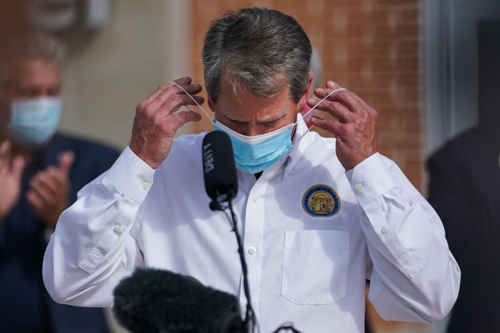 Brian Kemp, governor of Georgia, places a protective mask on his face during a 'Wear A Mask' tour stop in Dalton, Ga., on July 2, 2020.