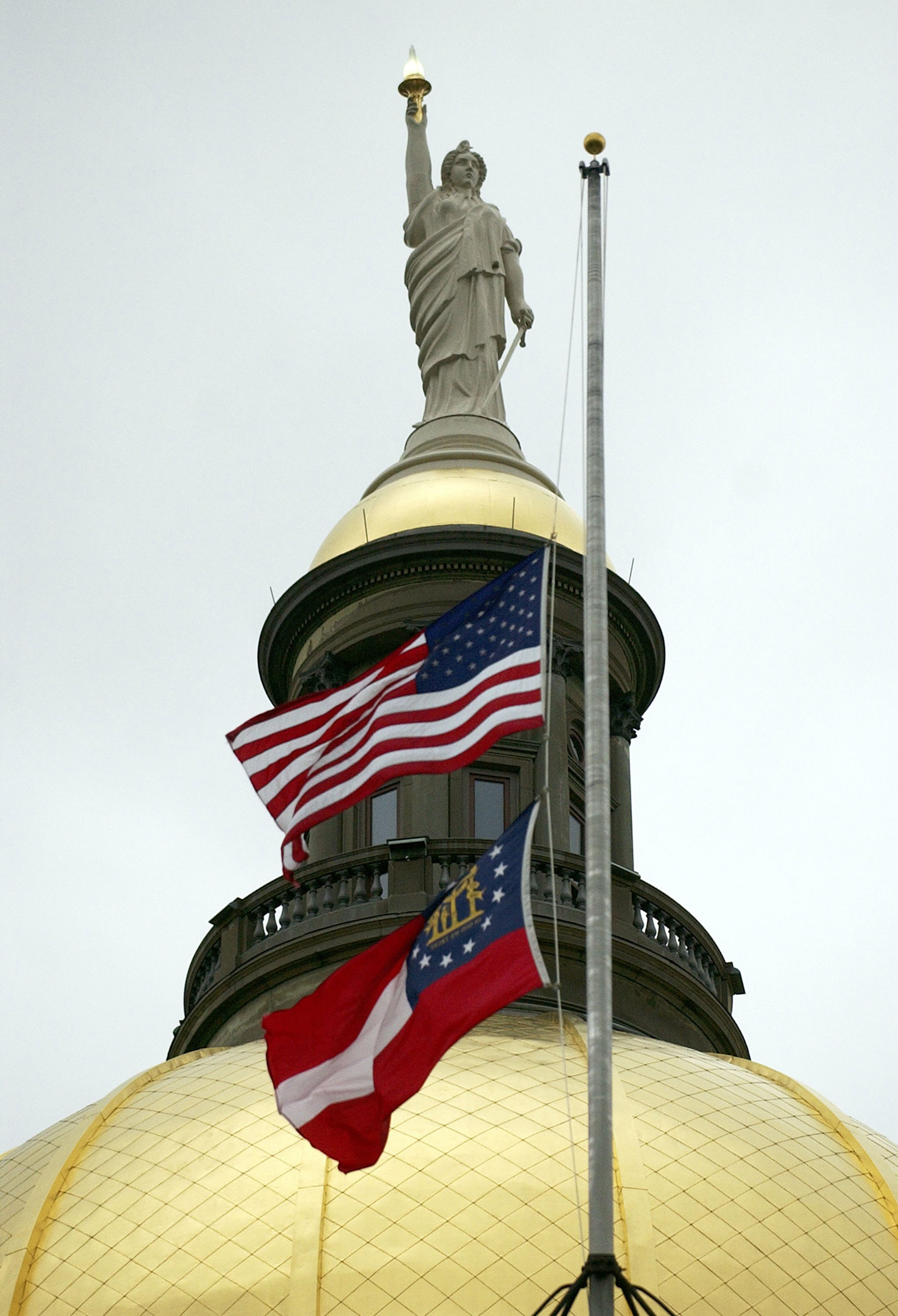 Flags atop Georgia's state Capitol fly at half staff in Atlanta on Feb. 4, 2006.