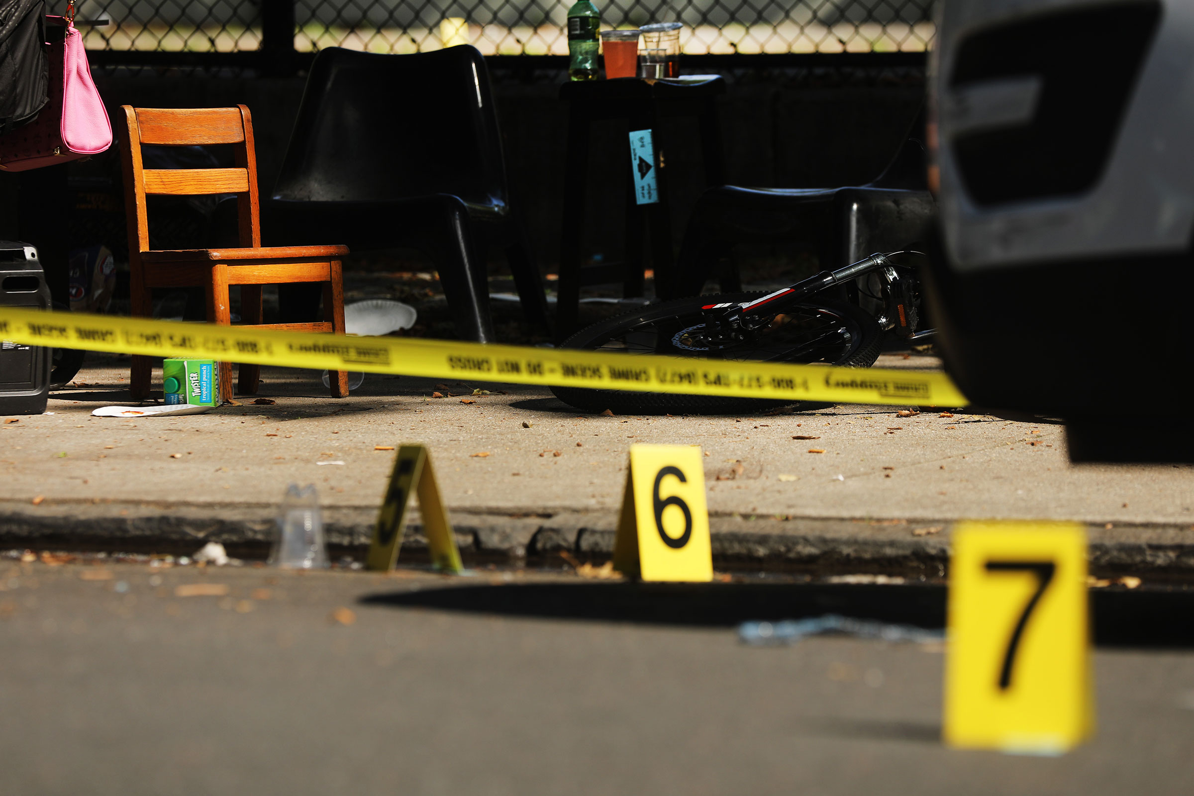 Police ballistic markers stand beside a child's chair and bicycle at a crime scene in Brooklyn where a one year old child was shot and killed on July 13, 2020 in New York City. The 1-year-old boy was shot near a playground during a Sunday picnic when gunfire erupted.