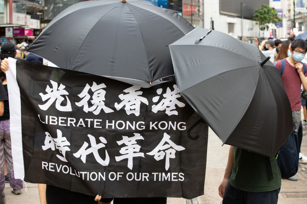 Protesters hold a flag  Liberate Hong Kong. Revolution of our times  while covering their face due to the now introduced National Security Law in Hong Kong, China, on July 1, 2020.