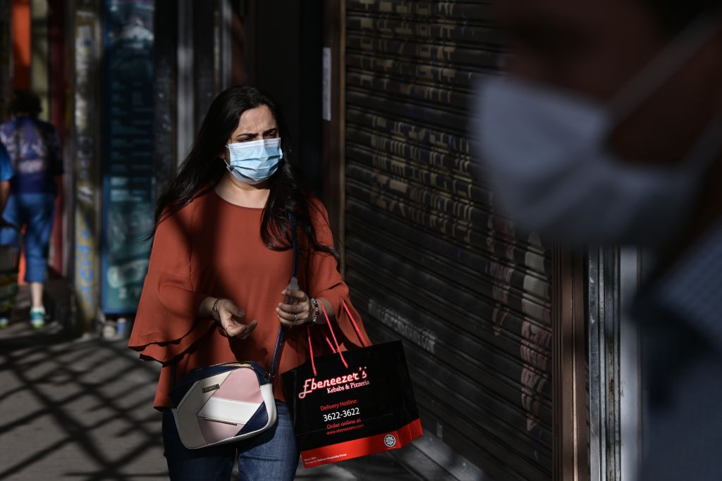 A woman holds a spray hand sanitiser and a takeout meal as she walks along a pavement in Hong Kong on July 27, 2020.