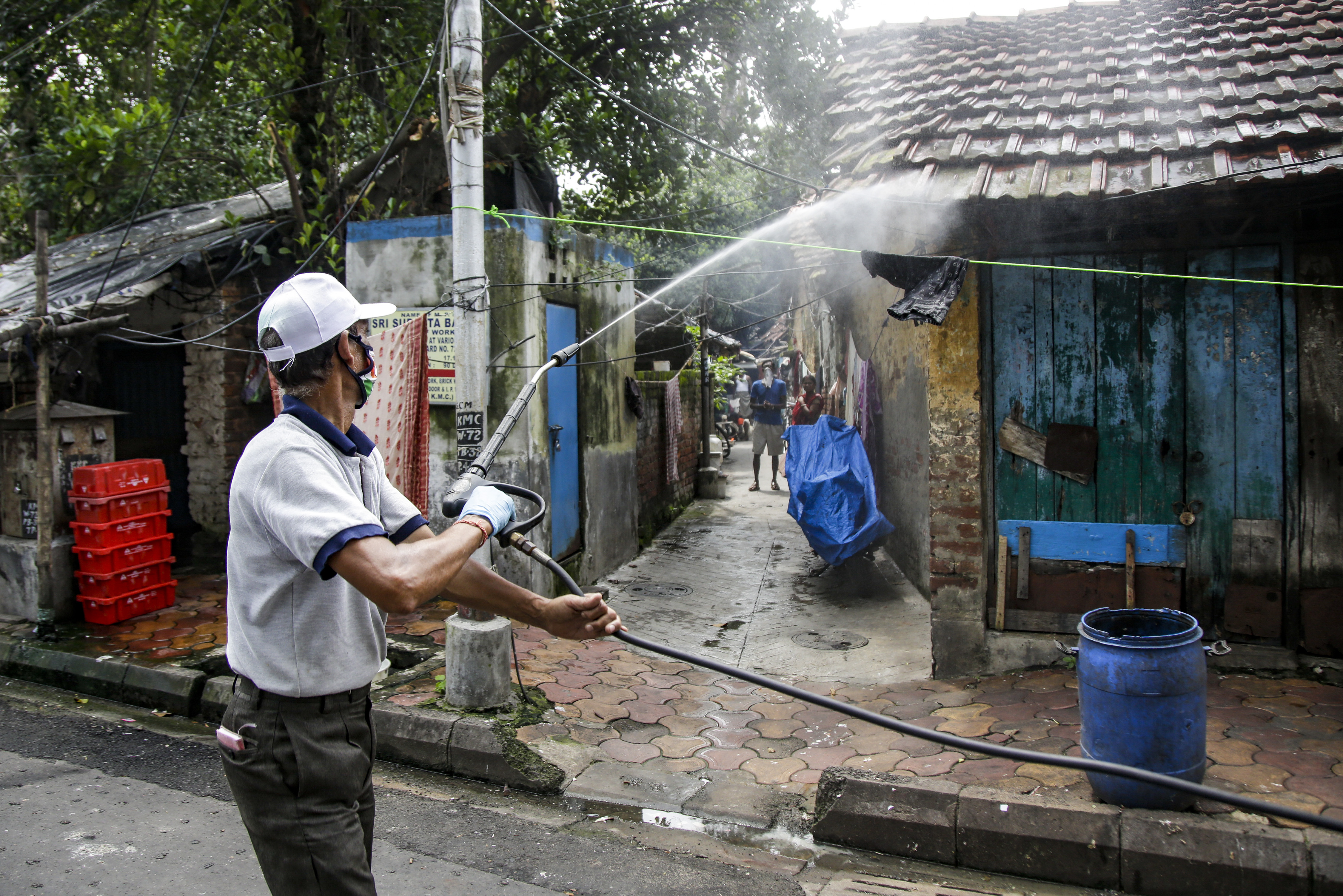 A civic worker disinfects an area inside a containment zone to prevent the spread of the coronavirus in Kolkata, India, Tuesday, July 14, 2020. Several Indian states imposed weekend curfews and locked down high-risk areas as the number of coronavirus cases surged past 900,000 on Tuesday.