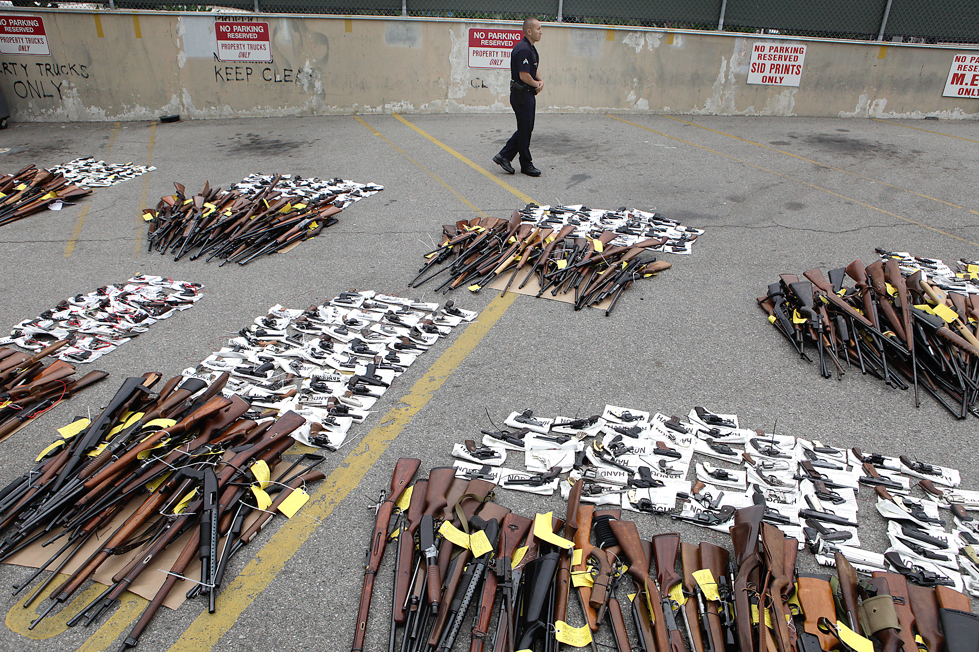 LAPD officer Manuel Ramirez stands guard near some of the nearly 1,700 weapons turned over the weekend at a news conference on May 11, 2009.
