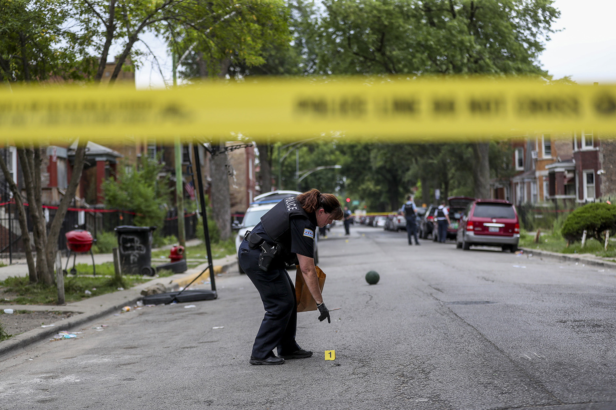 An officer collects evidence at the scene where an 8-year-old girl was shot on the 1000 block of North Monticello Avenue on Aug. 11, 2019 in Chicago.