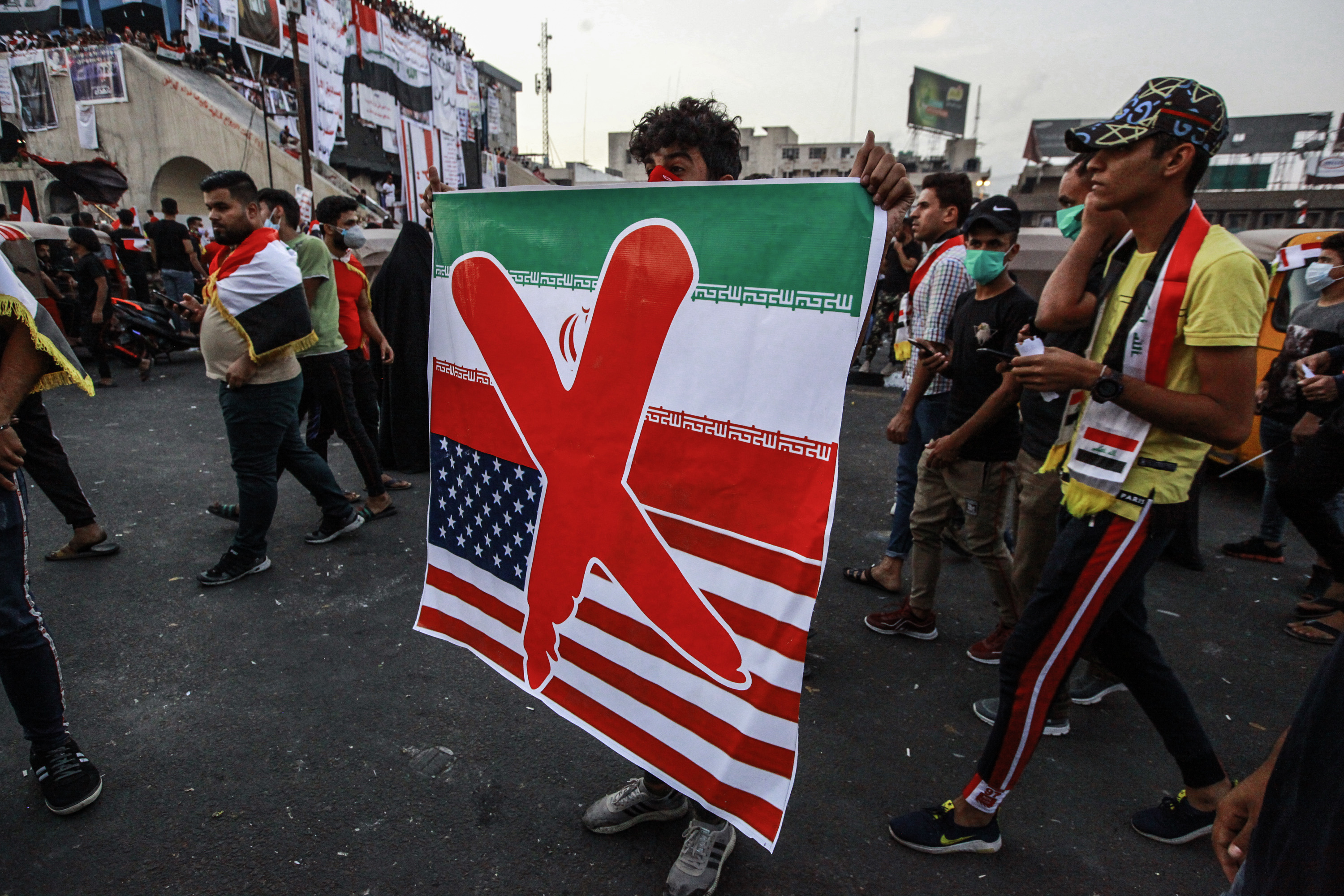 03 November 2019, Iraq, Baghdad: A protester holds a banner against the US and Iran during an anti-government protest near Tahrir Square. Photo by: Ameer Al Mohammedaw/picture-alliance/dpa/AP Images