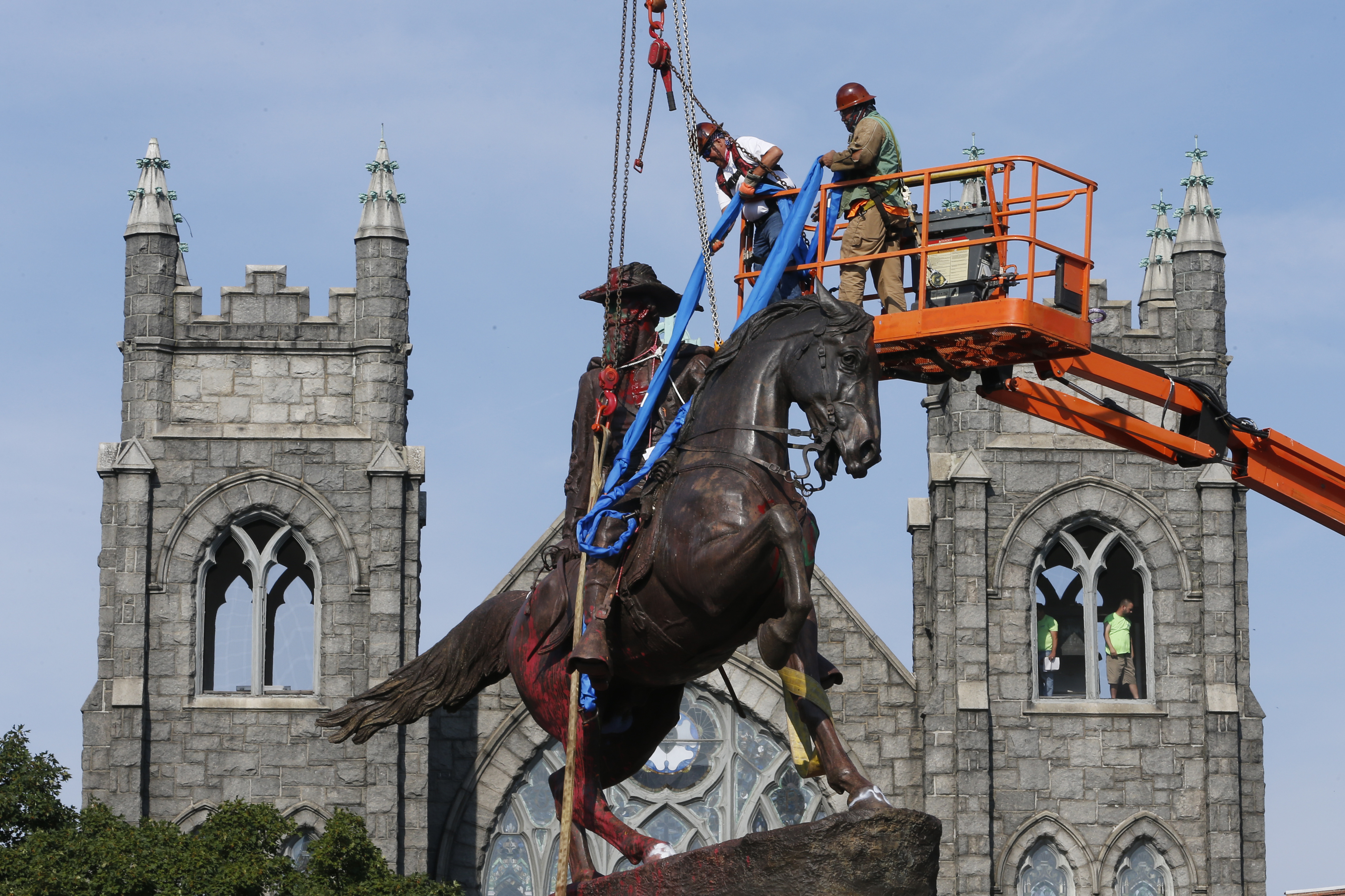 Crews attach straps to the statue Confederate General J.E.B. Stuart on Monument Avenue July 7, 2020, in Richmond, Va.
