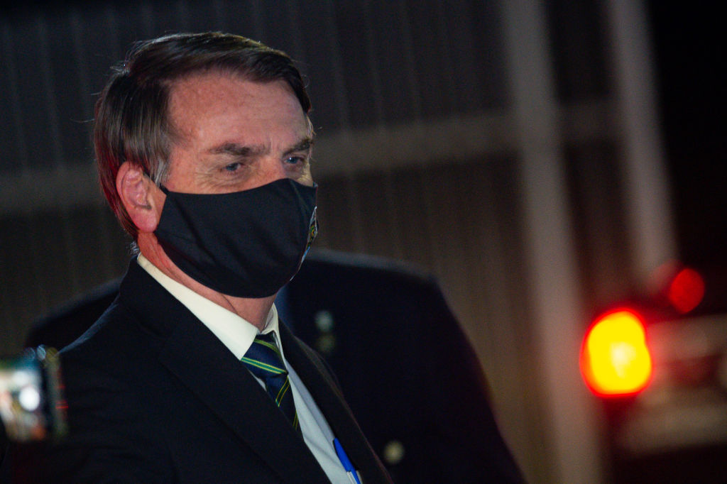 President of Brazil Jair Bolsonaro, wearing a face mask with a print of Brazil's Coat of Arms and written God above all, Brazil above all, reacts to supporters of his government who waited for him outside the Palácio do Alvorada amidstthe coronavirus (COVID-19) pandemic on May 27, 2020 in Brasilia.