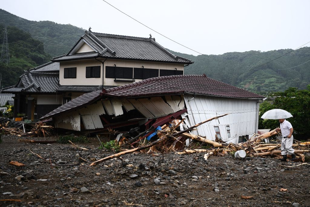 A man walks in a landslide site caused by heavy rain in Tsunagi, Kumamoto prefecture on July 7, 2020.