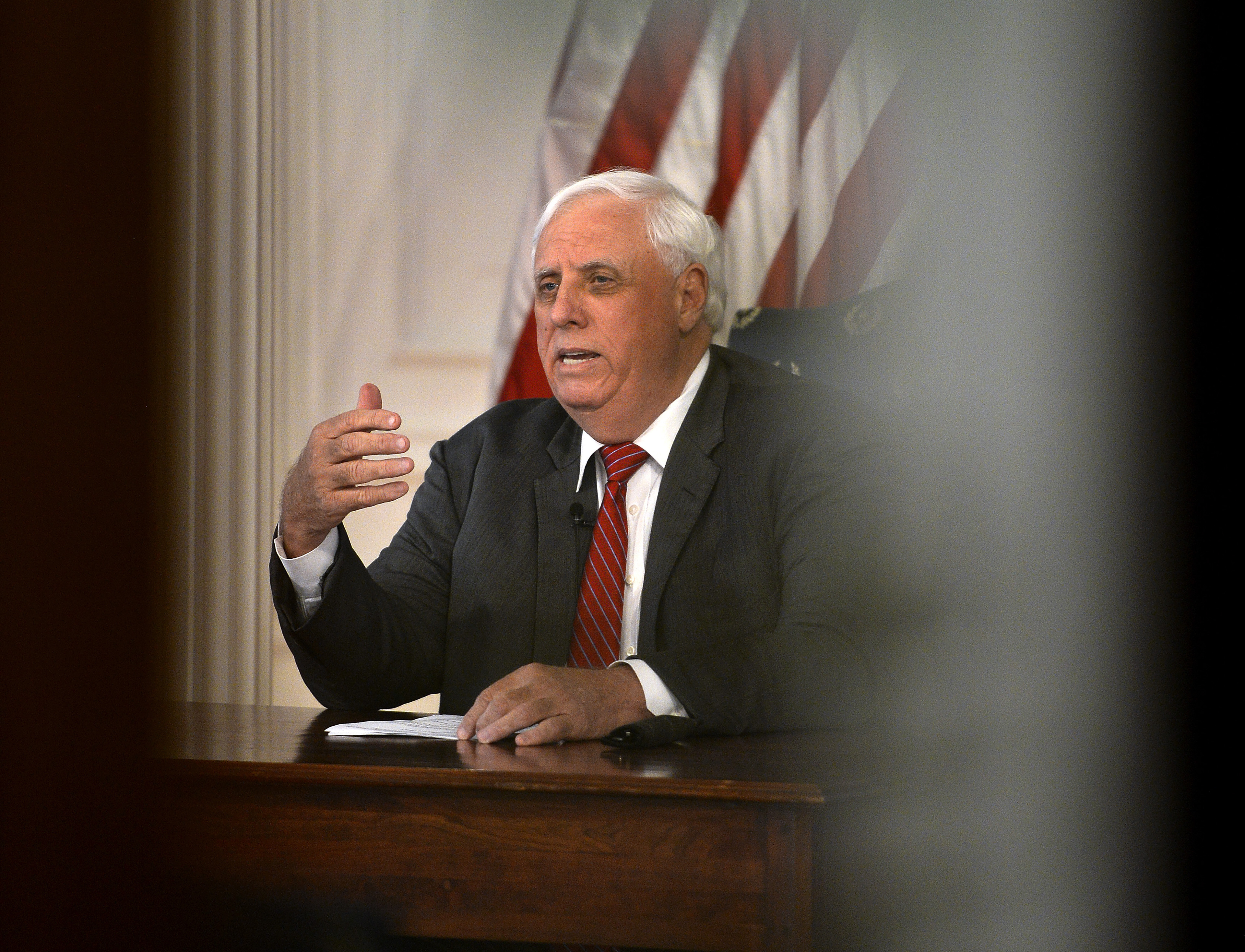 In this March, 23, 2020 file photo West Virginia Gov. Jim Justice issues a coronavirus stay at home order from his office in the State Capitol in Charleston, W. Va.