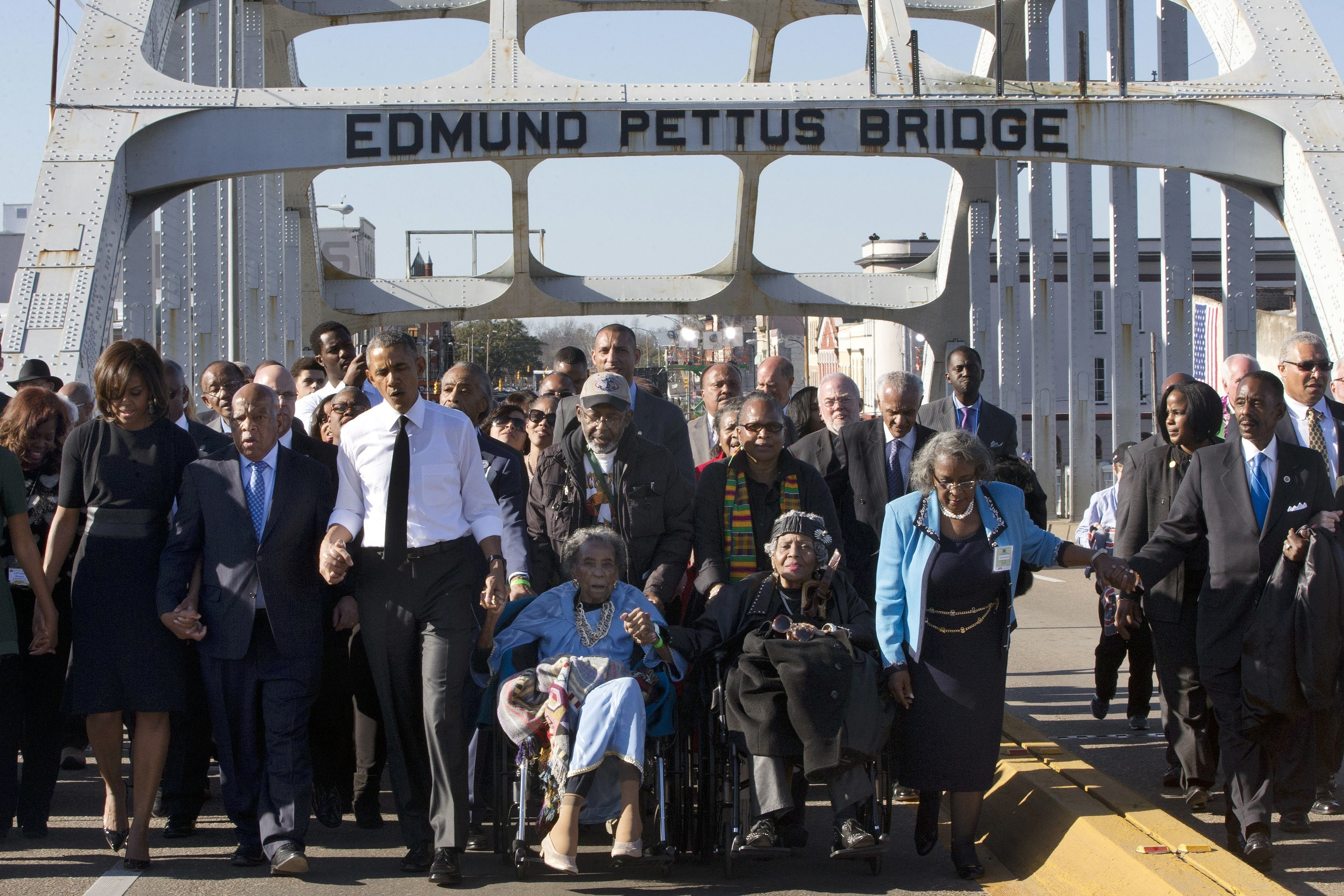 In this March 7, 2015, file photo, singing  We Shall Overcome,  President Barack Obama, third from left, walks holding hands with Amelia Boynton, who was beaten during  Bloody Sunday,  as they and the first family and others including Rep. John Lewis, D-Ga, left of Obama, walk across the Edmund Pettus Bridge in Selma, Ala., for the 50th anniversary of  Bloody Sunday,  a landmark event of the civil rights movement. Some residents in the landmark civil rights city of Selma, Ala., are among the critics of a bid to rename the historic bridge where voting rights marchers were beaten in 1965.