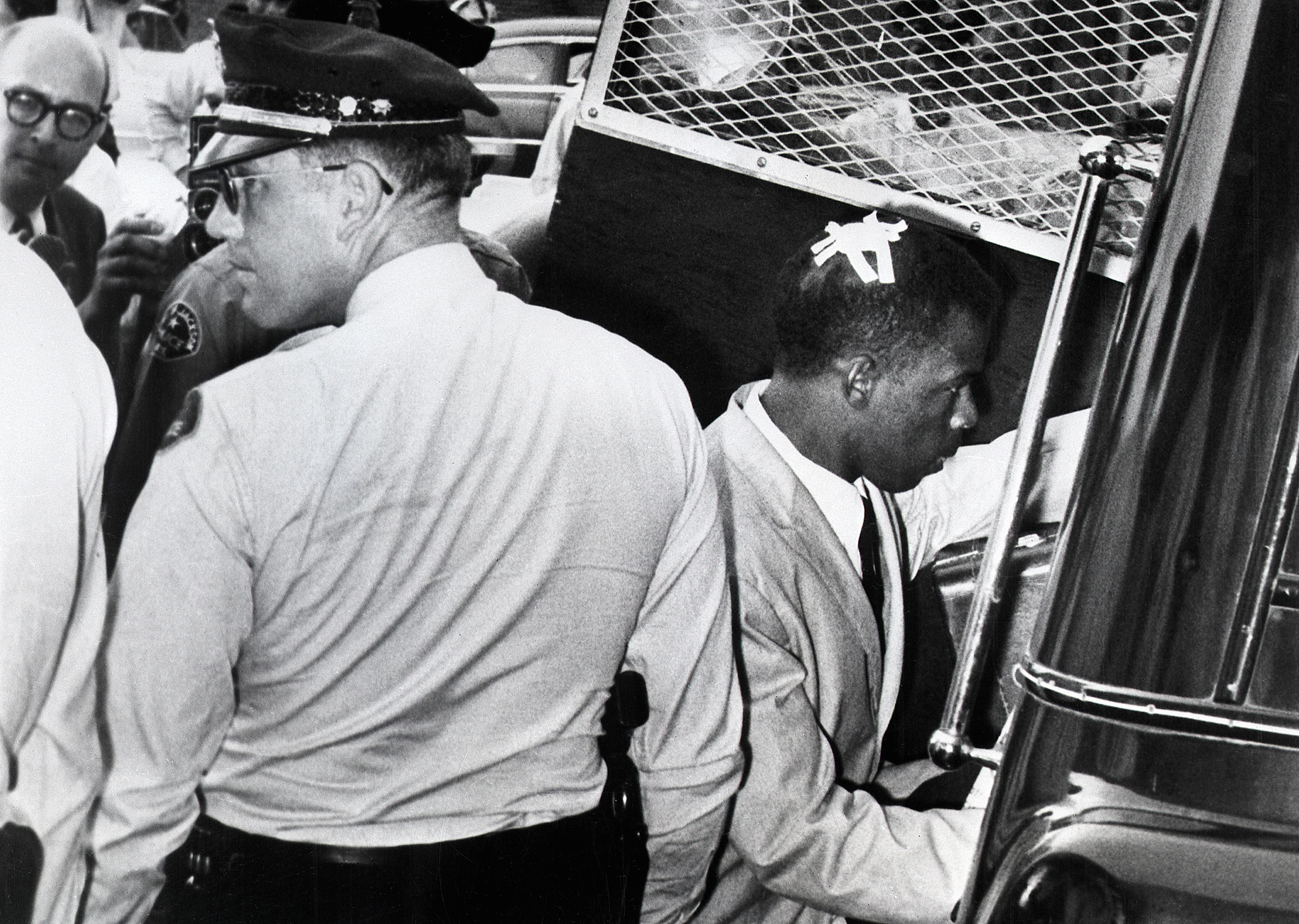 With an  X  made of tape still on his head, marking the spot where he was struck in Montgomery, Ala., John Lewis enters a police van after his arrest in Jackson, Miss., in May 1961.
