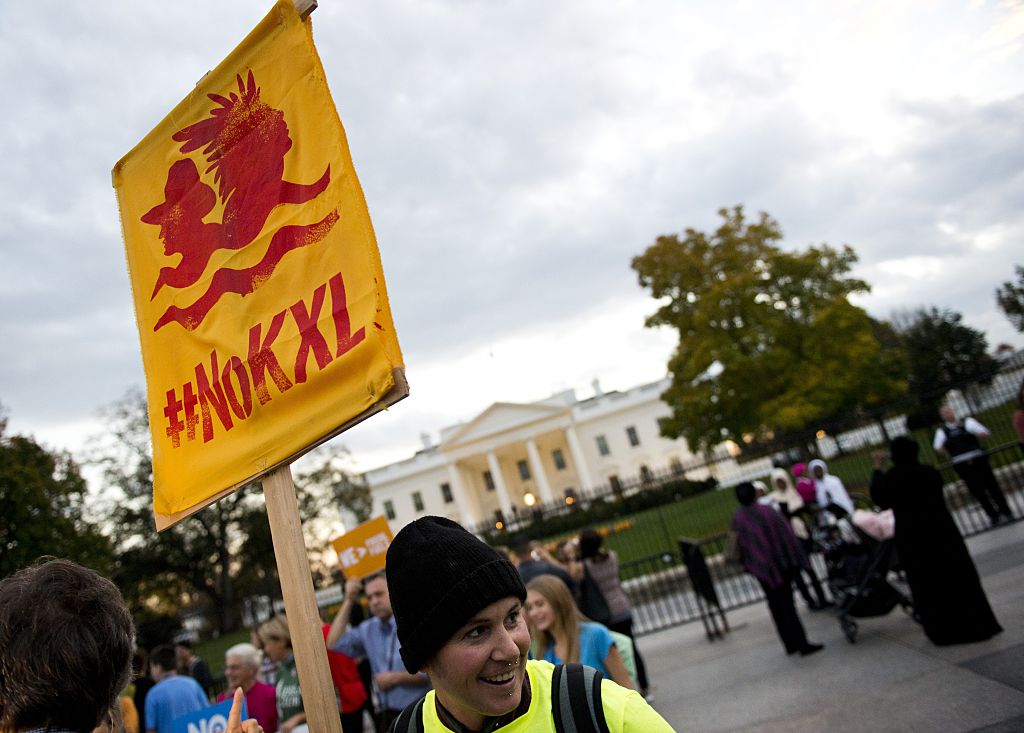 A demonstrator, celebrating US President Barack Obama's blocking of the Keystone XL oil pipeline, holds up a sign during a rally in front of the White House in Washington, D.C. on November 6, 2015.