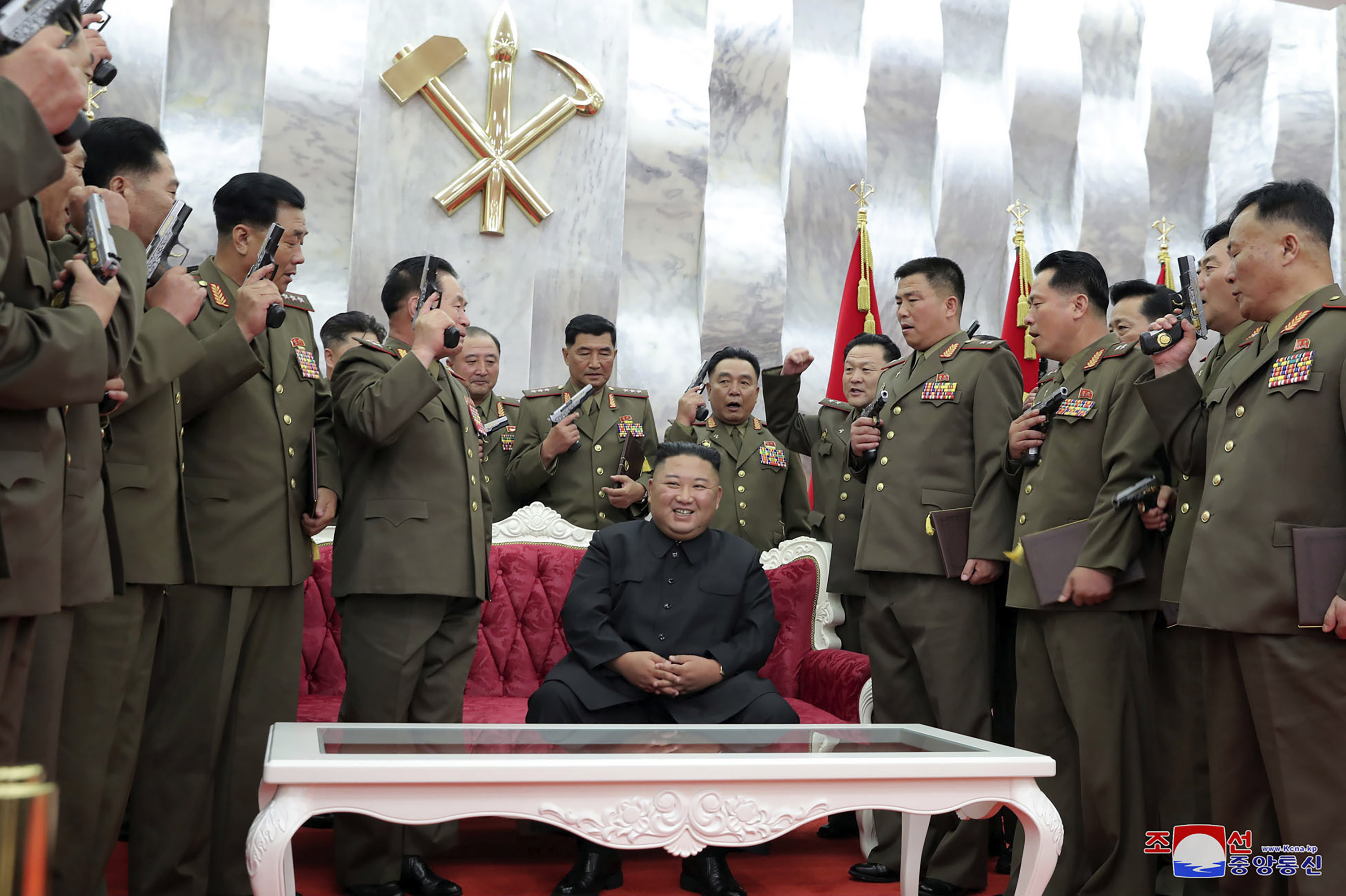 """In this Sunday, July 26, 2020, photo released by the North Korean government, North Korean leader Kim Jong Un, sitting center,  is surrounded by senior military officials holding """"Paektusan"""" commemorative pistols they received from Kim during a ceremony in Pyongyang, North Korea. Independent journalists were not given access to cover the event depicted in this image distributed by the North Korean government. The content of this image is as provided and cannot be independently verified. Korean language watermark on image as provided by source reads:  KCNA  which is the abbreviation for Korean Central News Agency."""