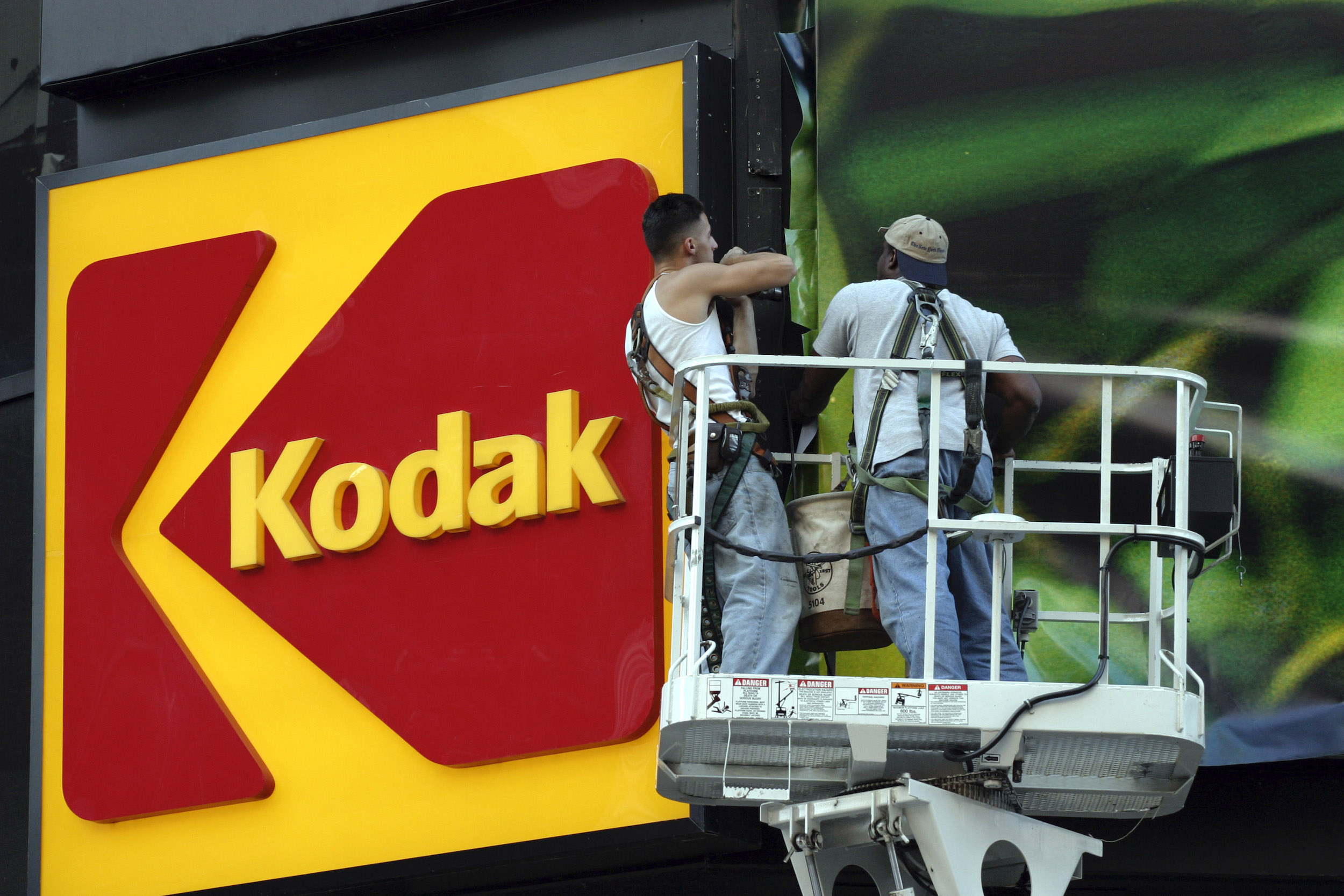 Workers stand near the KODAK billboard at Times Square, New York City.
