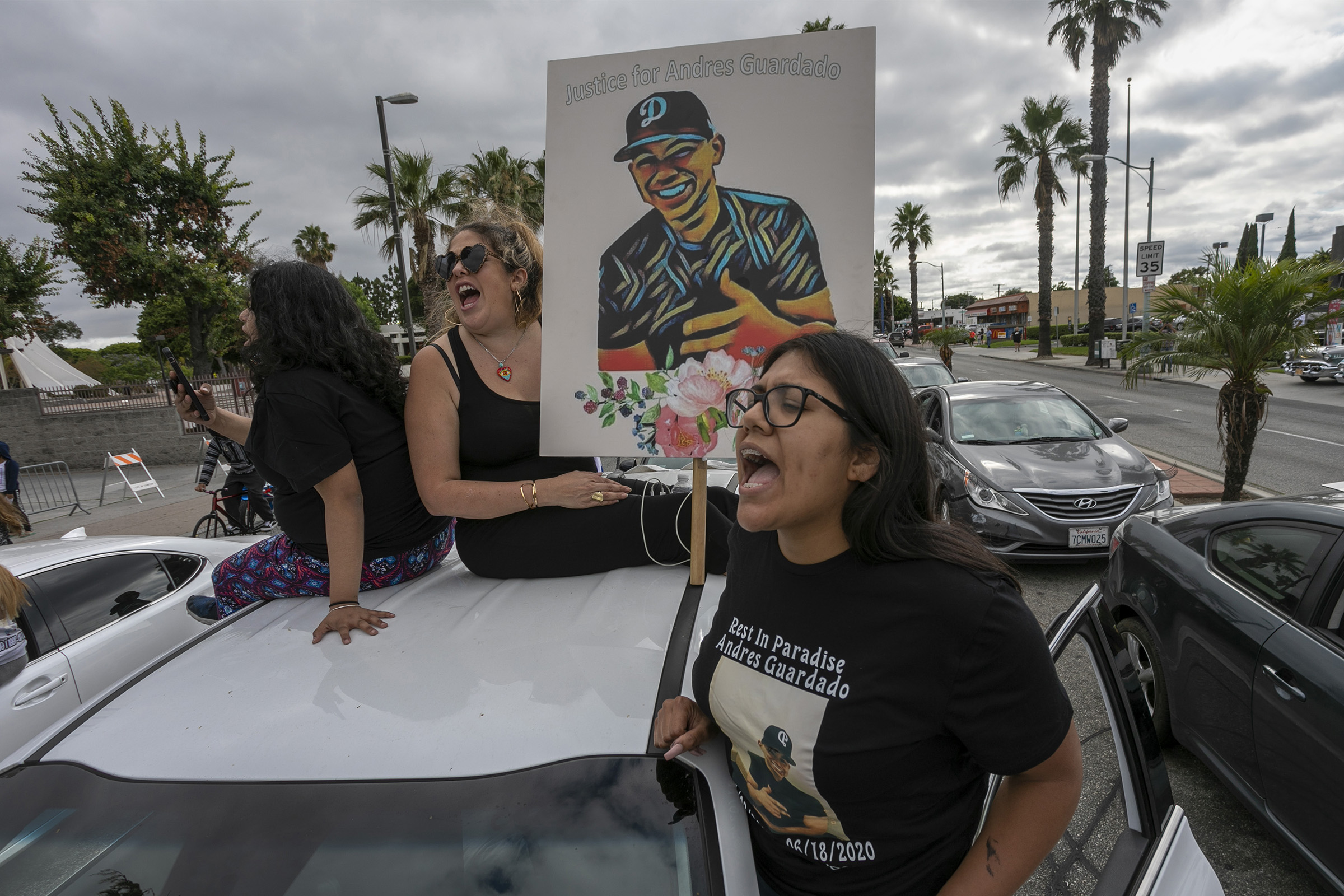 A woman holds a placard as activists and relatives of Andres Guardado, who was shot and killed by a sheriff's deputy in Gardena, rally to call on the city to rescind its policing contract, in Compton, California, on June 28, 2020.