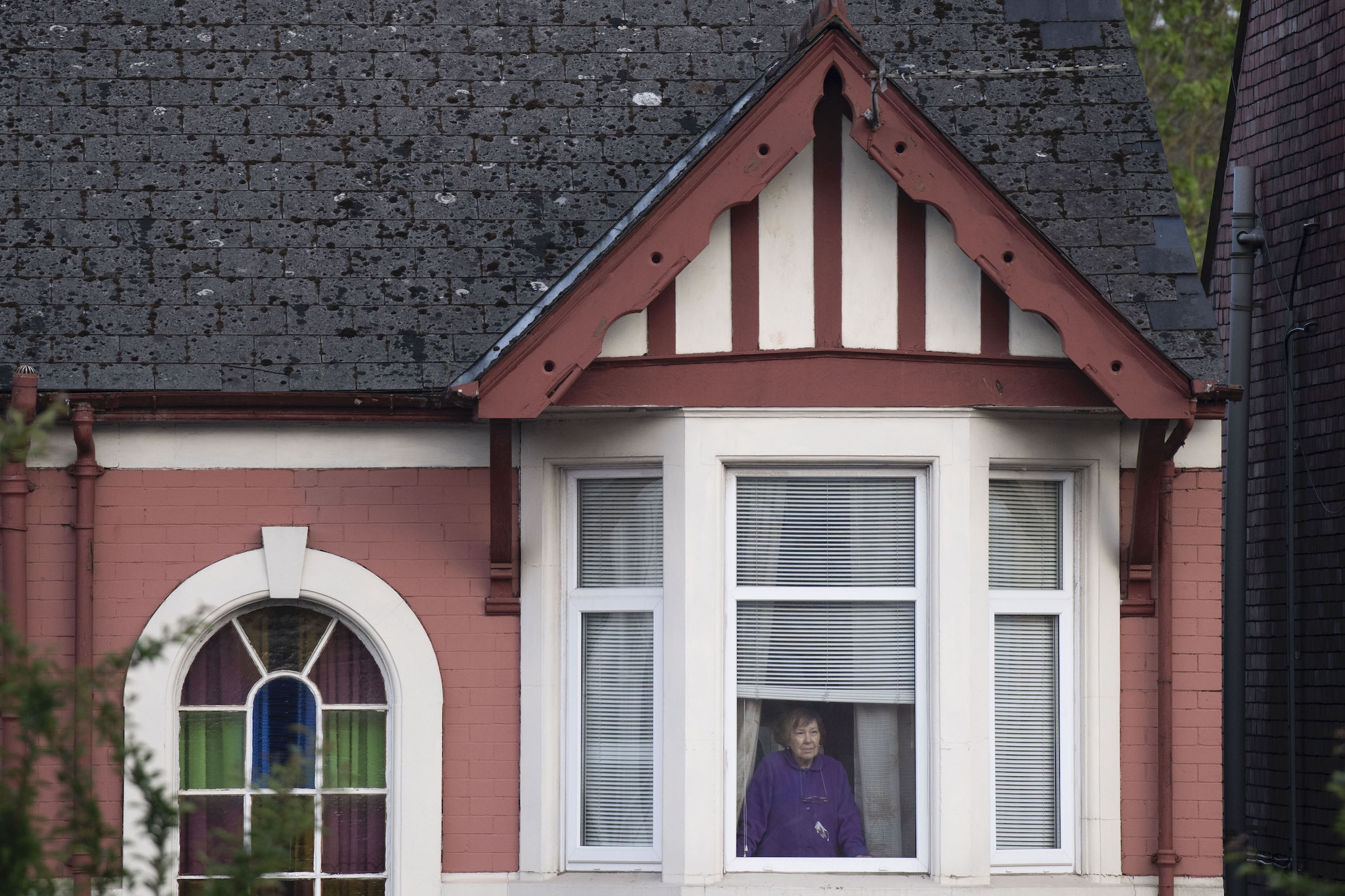 A woman looks on from the upstairs window of a house opposite the Royal Gwent Hospital as people gather to clap key workers on April 23, 2020 in Newport, U.K.