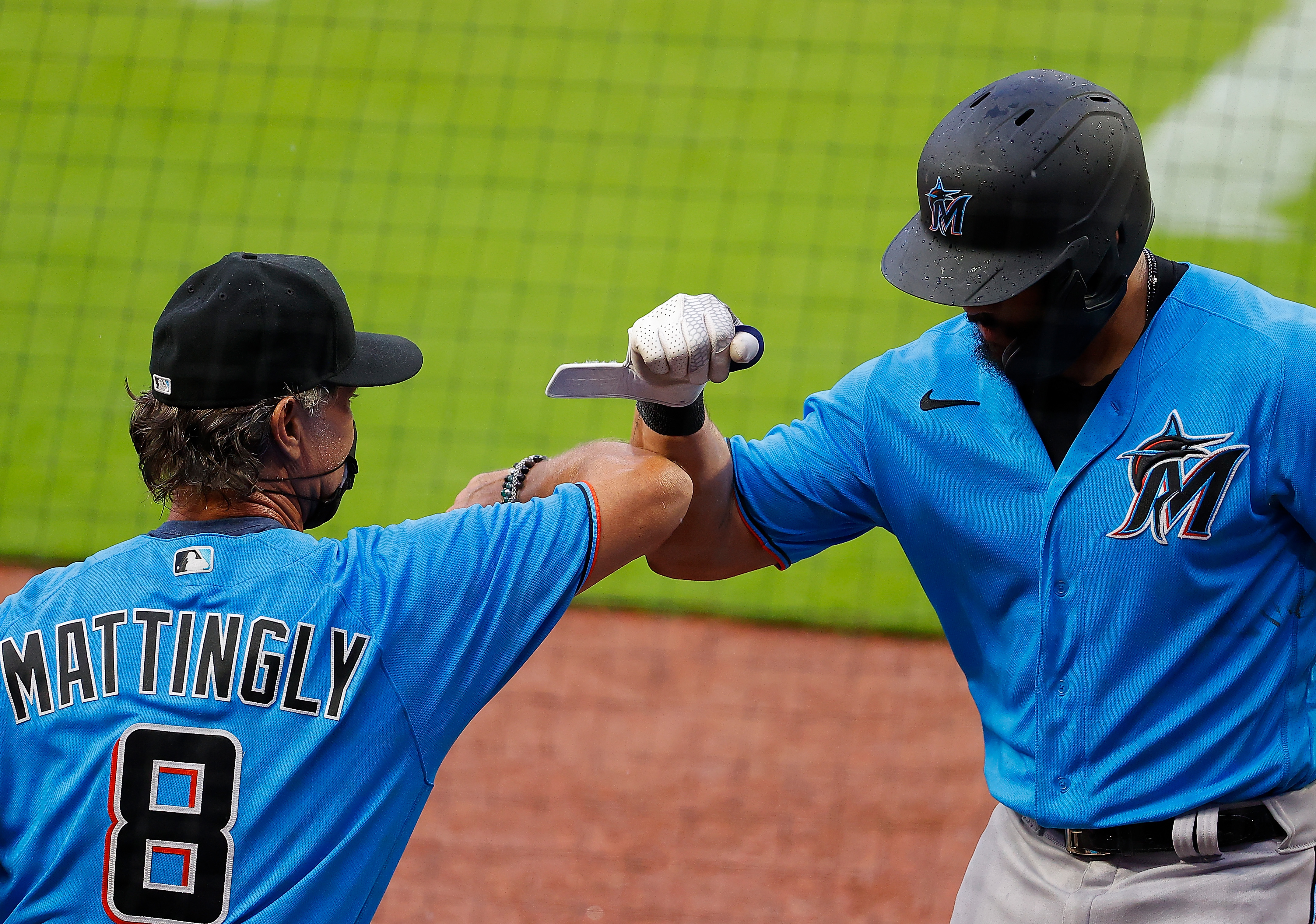 Jorge Alfaro #38 of the Miami Marlins reacts with manager Don Mattingly #8 after hitting a solo homer in the third inning against the Atlanta Braves during an exhibition game at Truist Park on July 21, 2020 in Atlanta, Georgia.