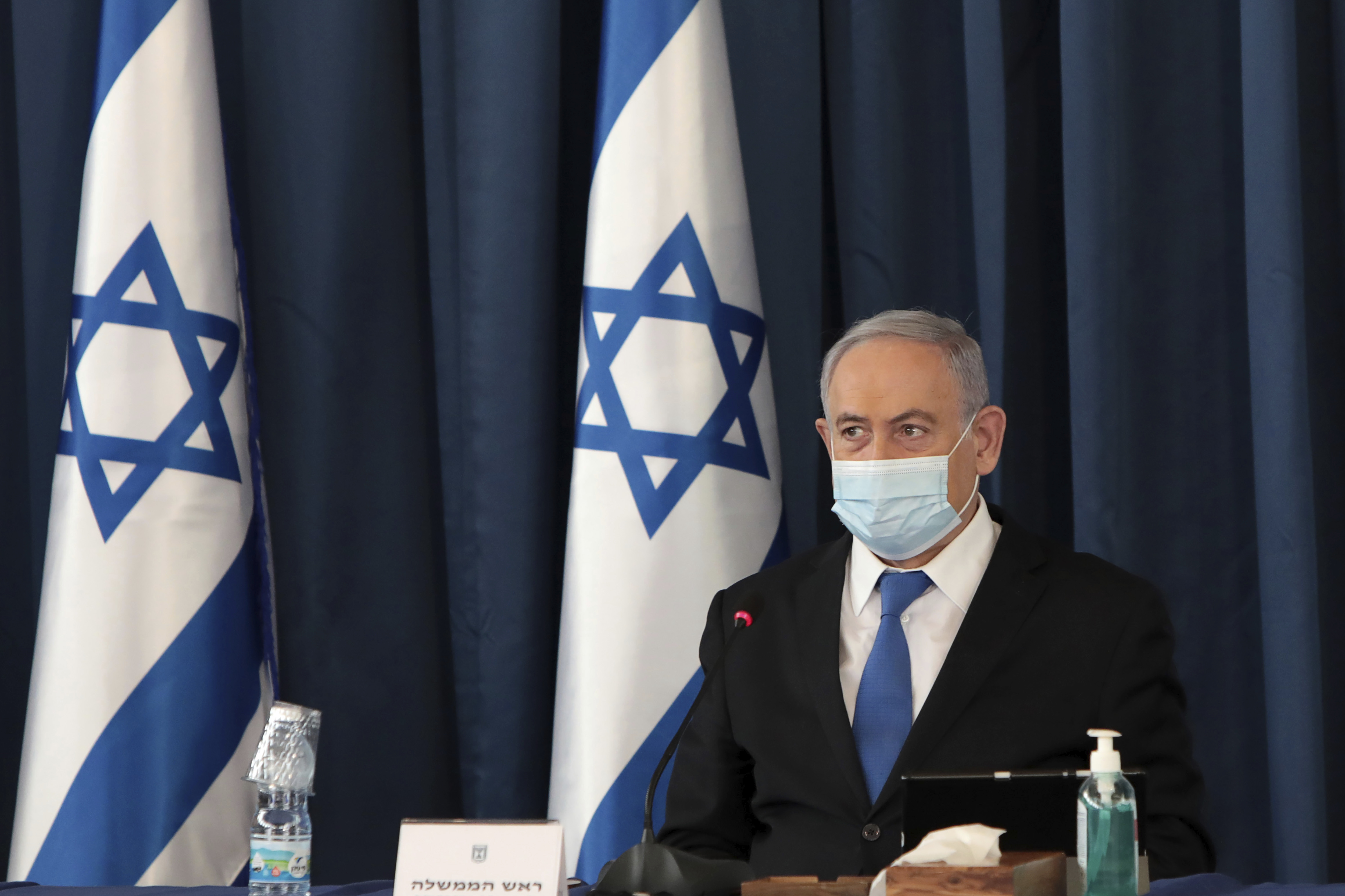 Israeli Prime Minister Benjamin Netanyahu wears a face mask to help prevent the spread of the coronavirus as he opens the weekly cabinet meeting, at the foreign ministry, in Jerusalem, July 5, 2020.