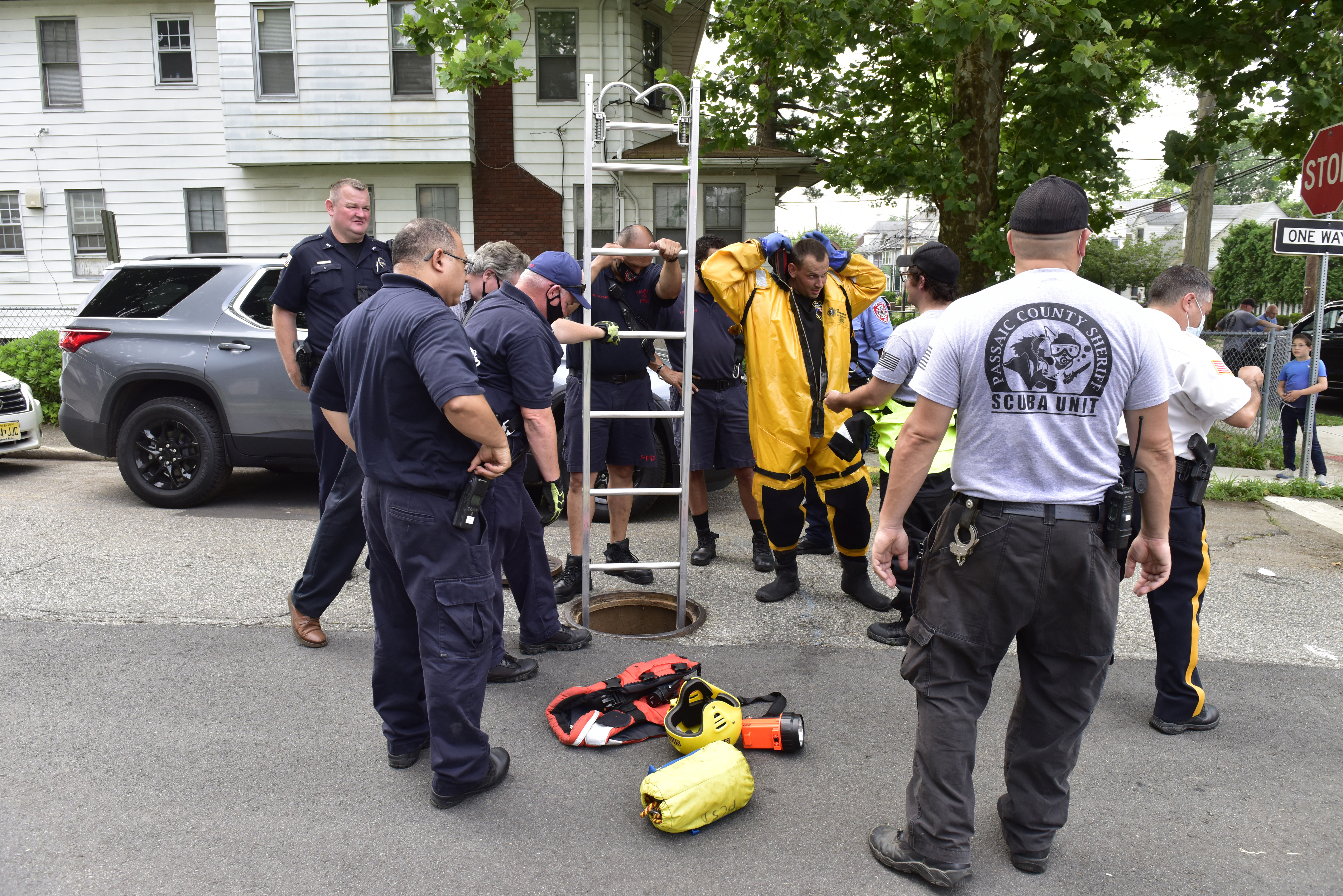 Emergency personnel search to find a Toyota Prius that was swept away into a canal on Monday July 6, 2020 in Passaic, N.J.