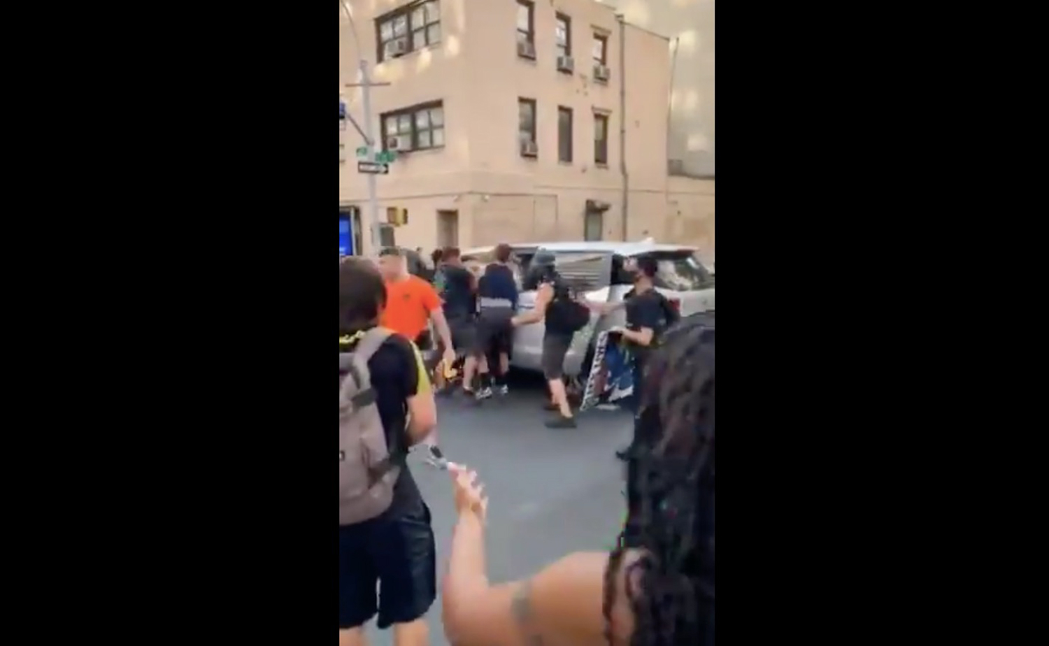 NYPD officers pushing a protester into an unmarked van on July 28, 2020.