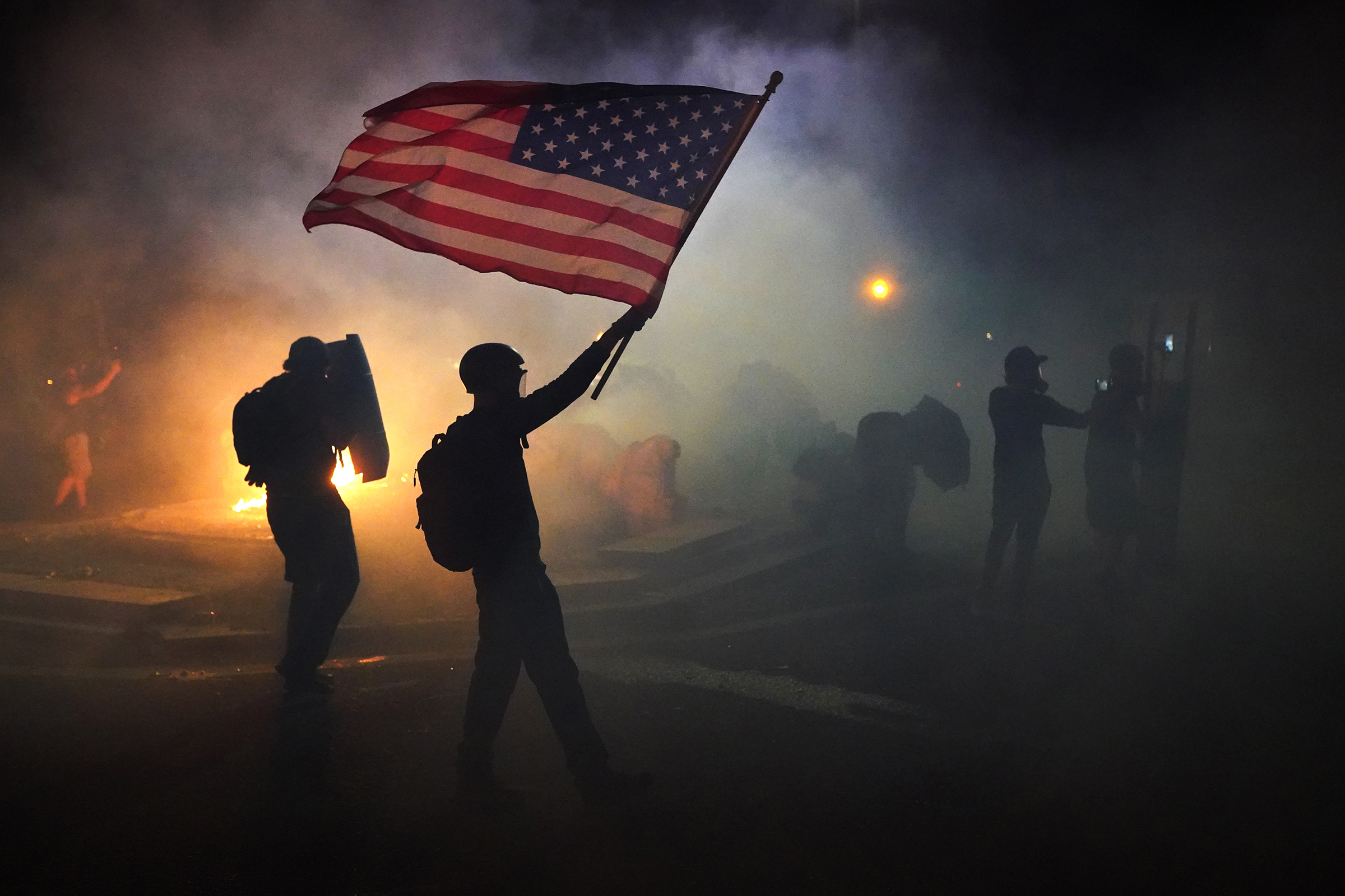 A protester flies an American flag while walking through tear gas fired by federal officers during a protest in Portland, Oregon on July 21, 2020.