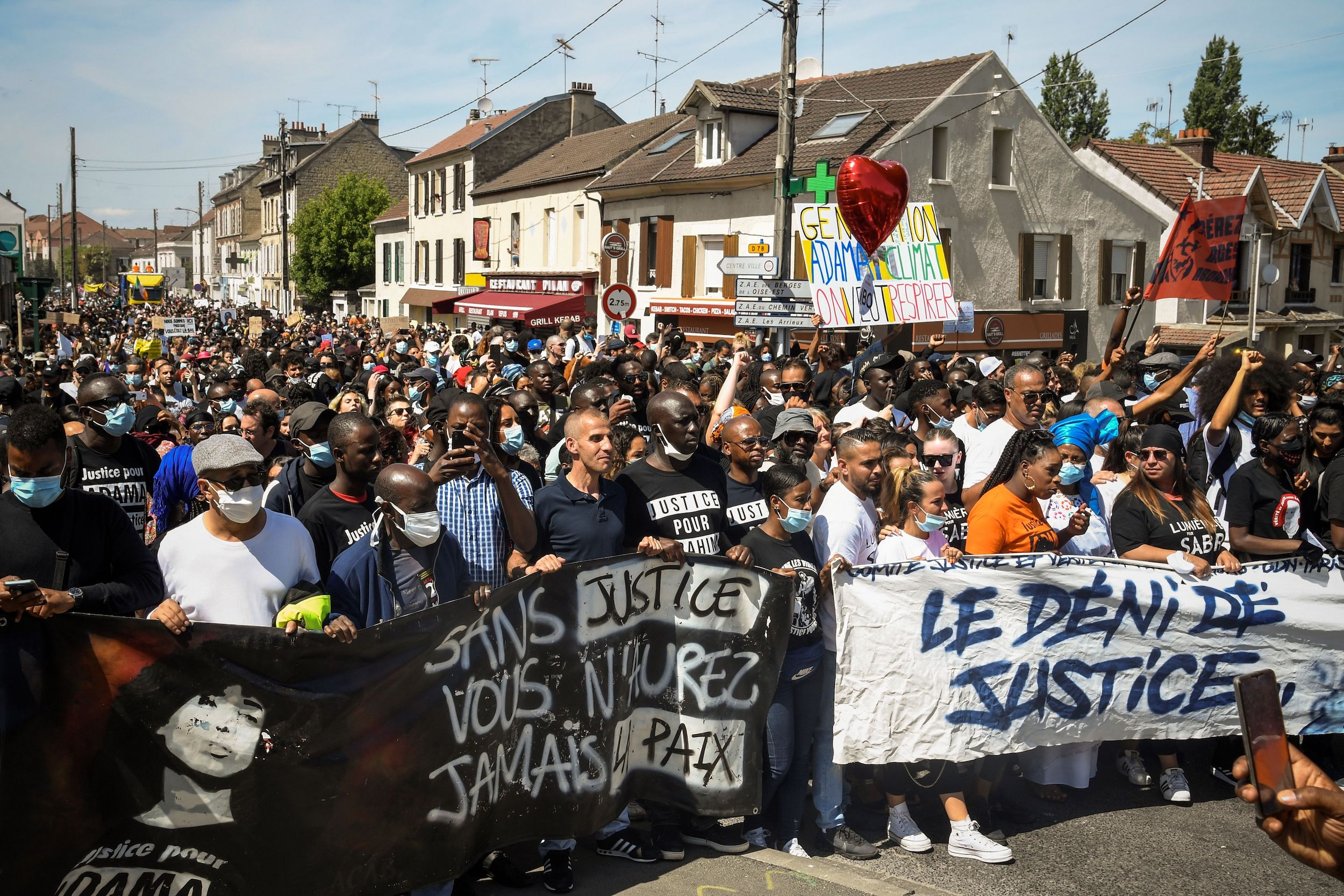 People take part in a march called by several civil rights and ecologist associations to commemorate Adama Traore, a black man who died in police custody four years ago, and to protest against police violence on July 18, 2020 in the Parisian suburban city of Beaumont-sur-Oise.