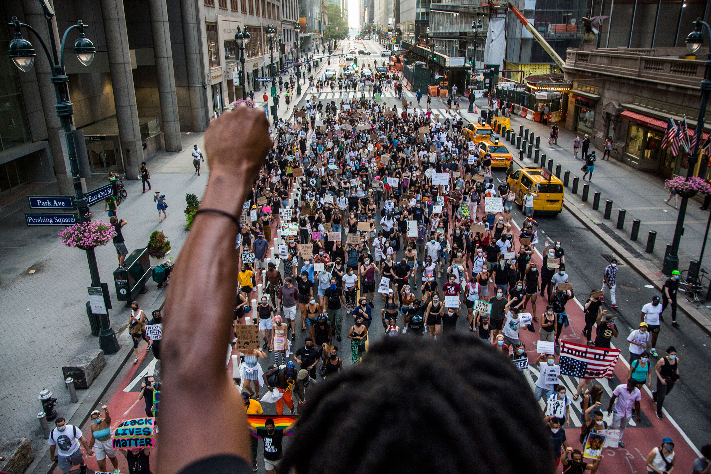 A man raises his arm in support of the crowd of protesters marching in downtown New York, NY on July 26, 2020.