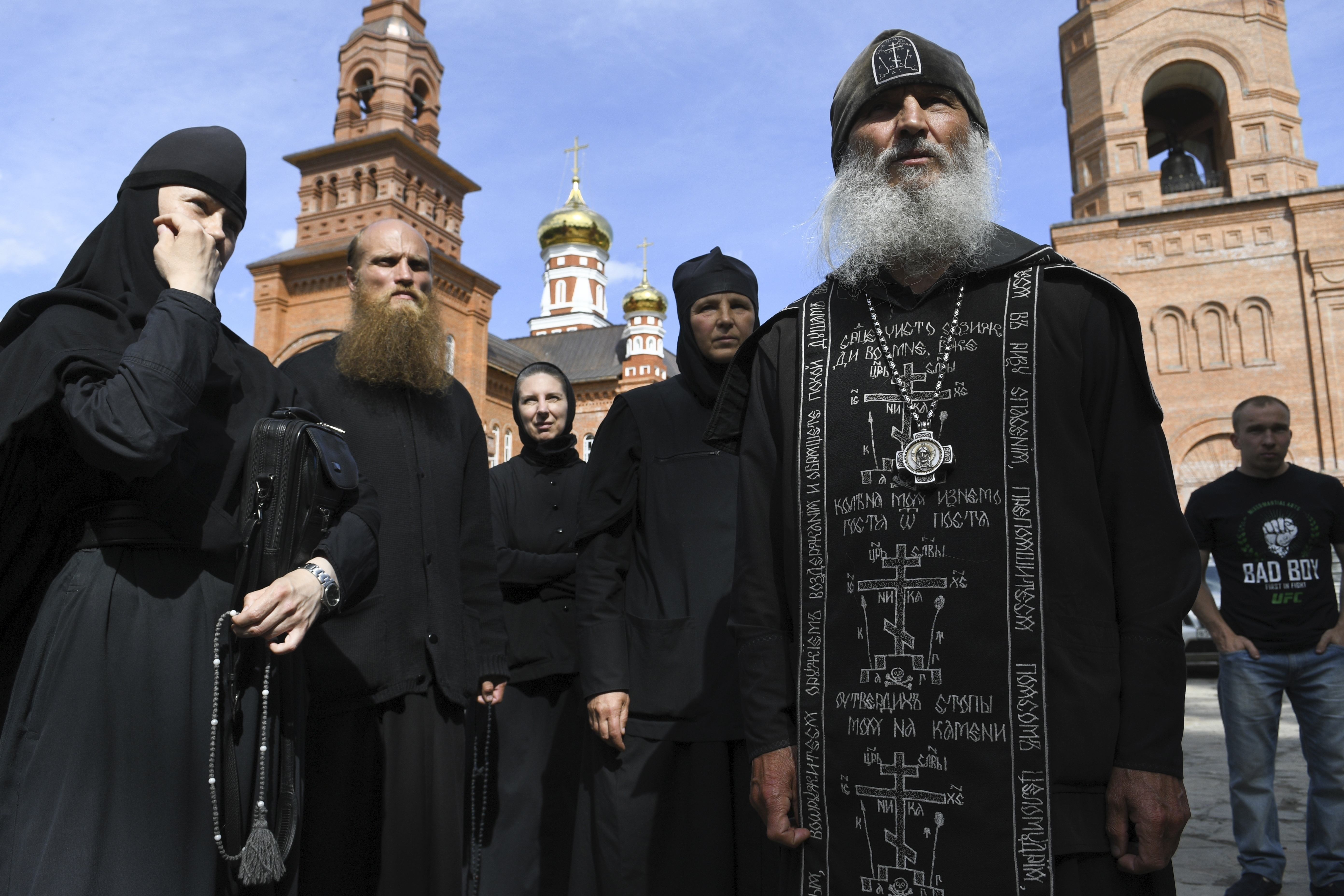 Father Sergiy, a Russian monk who has defied the Russian Orthodox Church's leadership, right, speaks to journalists in Russian Ural's Sredneuralsk, Russia on June 17, 2020.