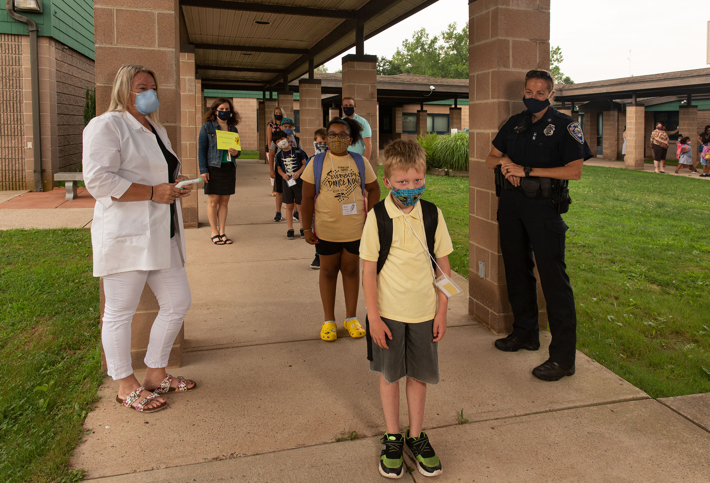Nurse Sarah Ladd and school resource officer Kristen Tyrseck ensure kids keep a safe distance apart as they enter Wesley Elementary School                      in Middletown, Conn.