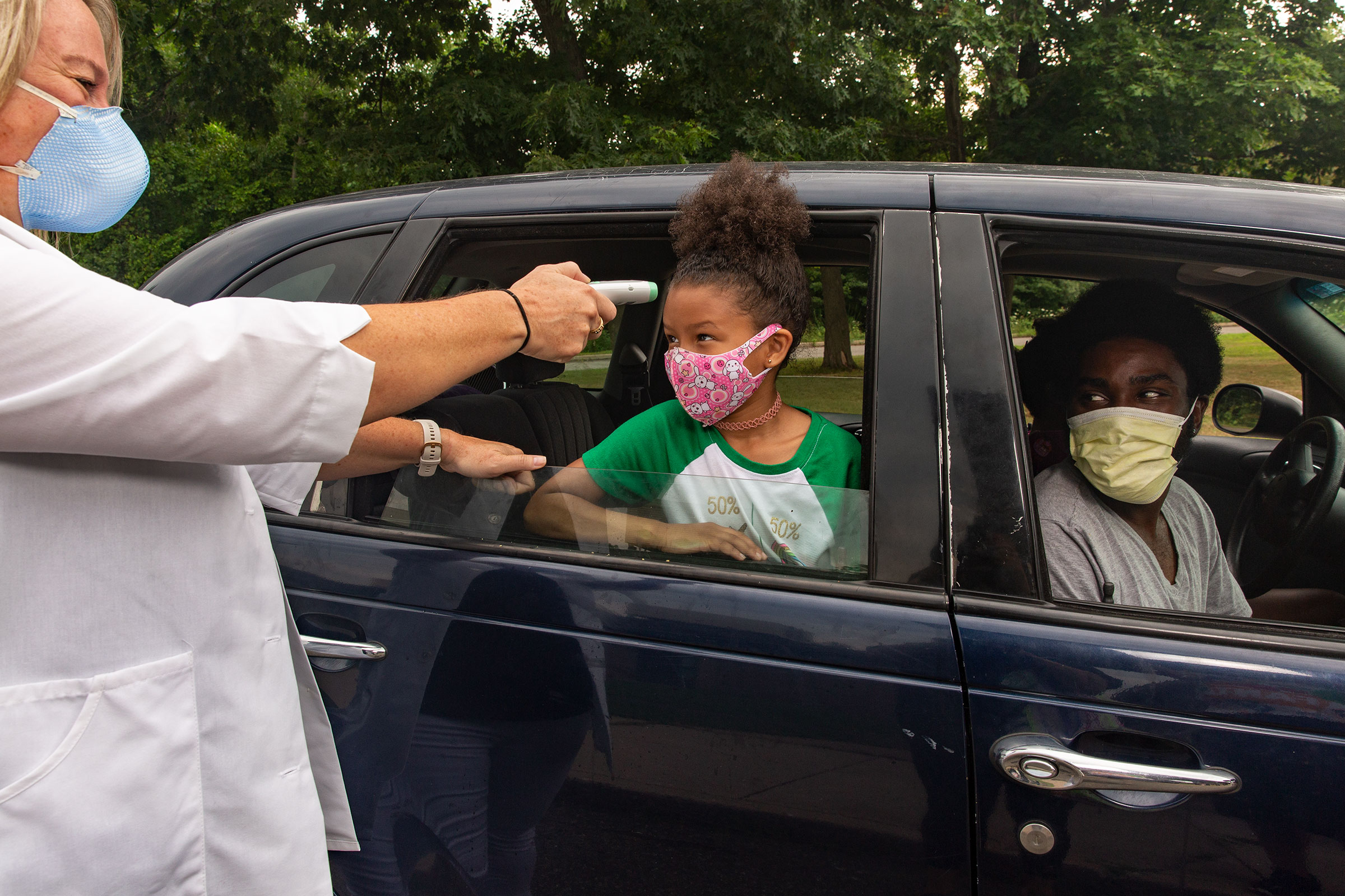 Nurse Sarah Ladd takes 5-year-old Nova Wright's temperature as she's dropped off at school