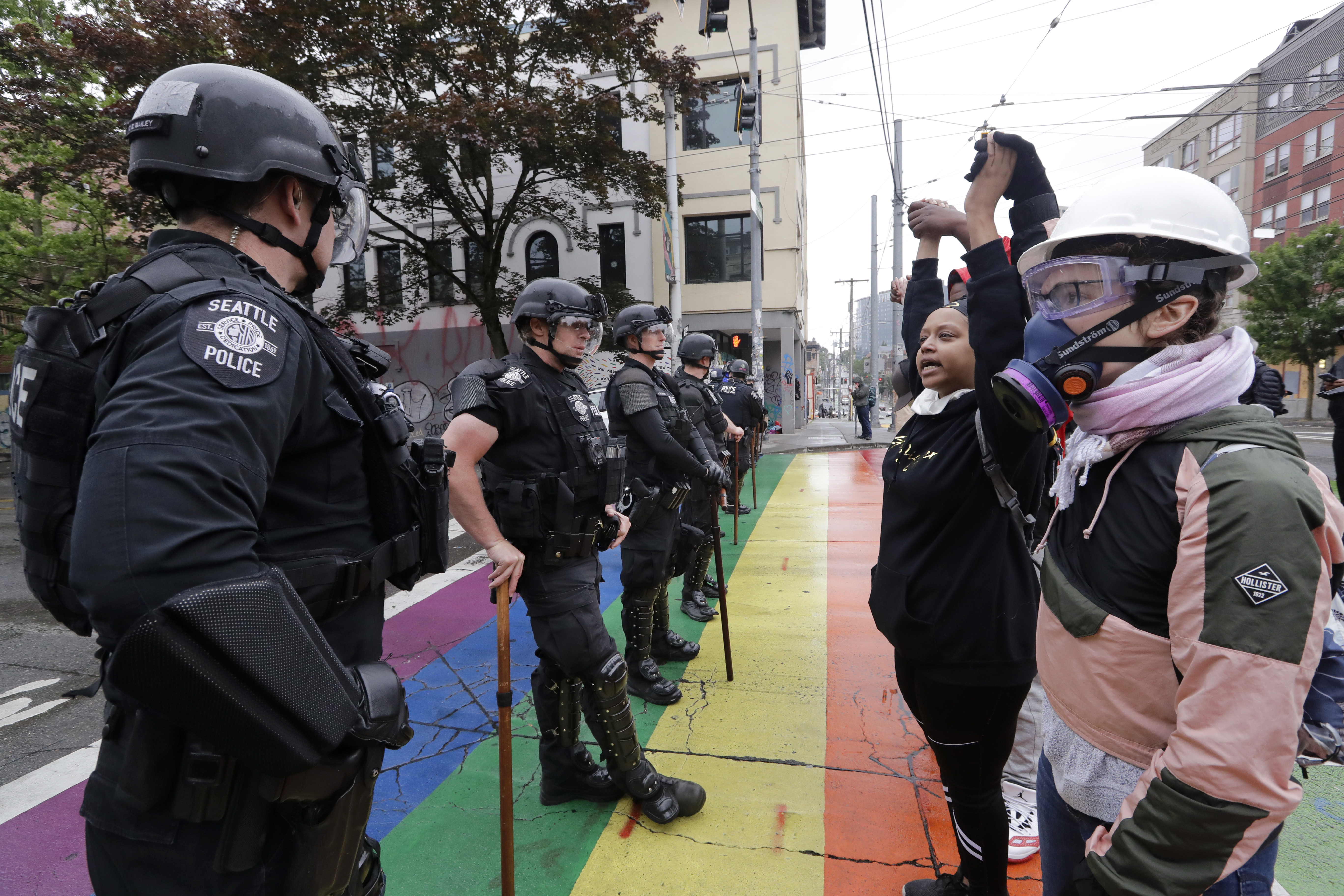 Protesters hold hands in front of a line of police officers blocking a street on July 1, 2020, in Seattle. The  Capitol Hill Occupied Protest  zone was set up near downtown following the death of George Floyd while in police custody in Minneapolis.