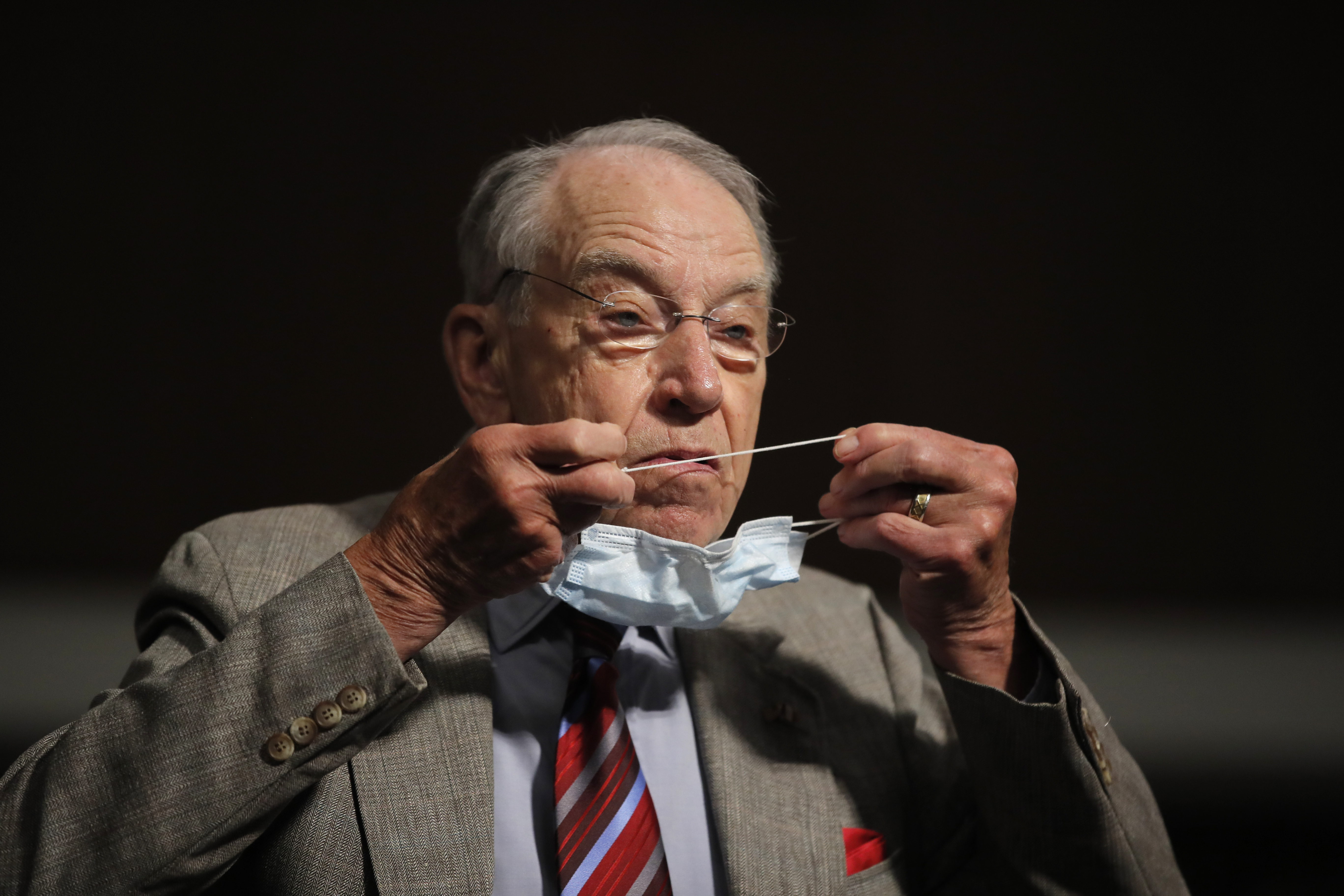 Sen. Chuck Grassley, R-Iowa, puts on a face mask during a Senate Judiciary Committee on Capitol Hill in Washington on June 11, 2020.