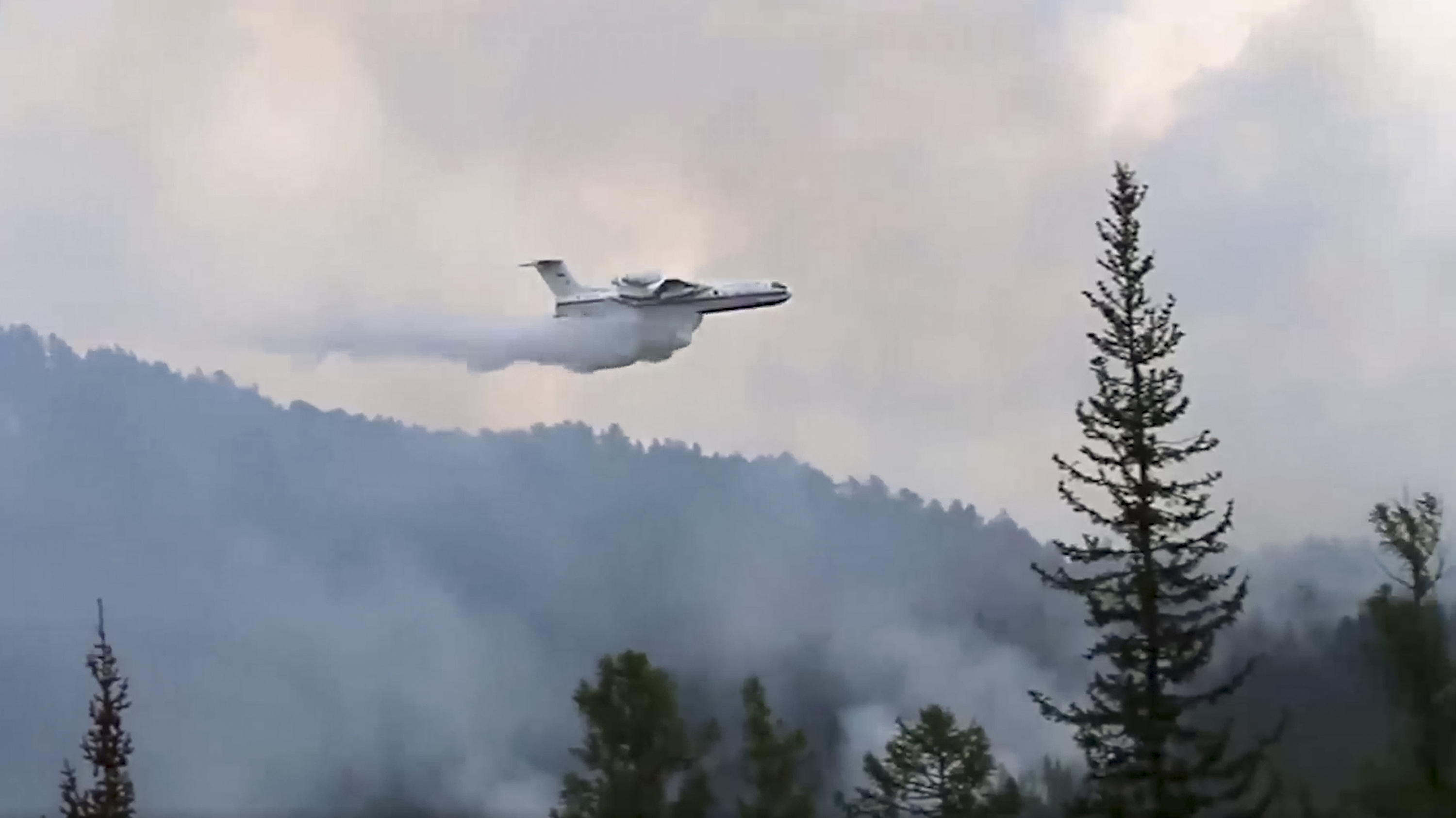 A Russian Emergency Ministry multipurpose amphibious aircraft releasing water to extinguish the fire in the Trans-Baikal National Park in Buryatia, southern Siberia, Russia, on July 9, 2020.