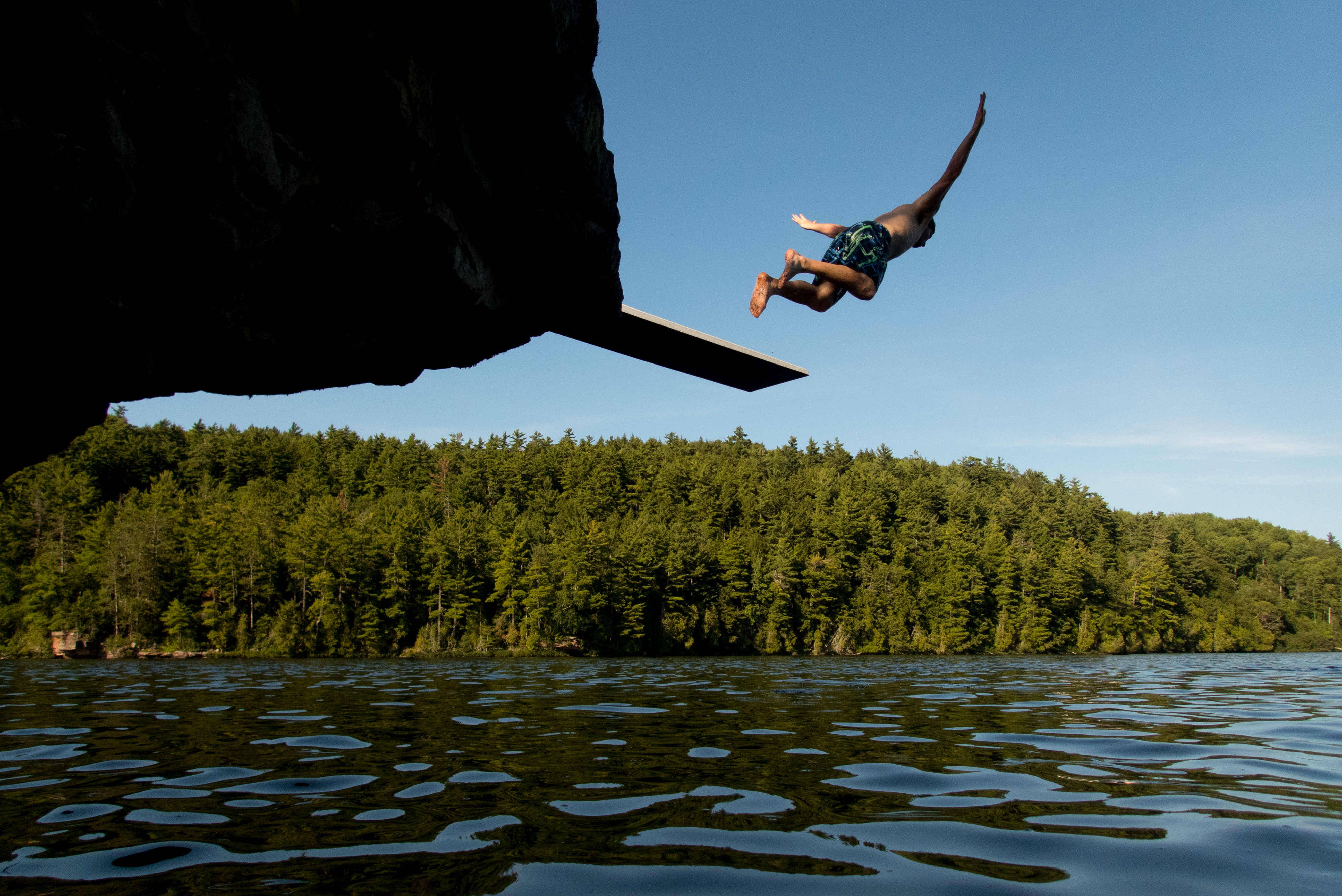 A young adult jumping off a diving board into a lake in Michigan's Upper Peninsula.