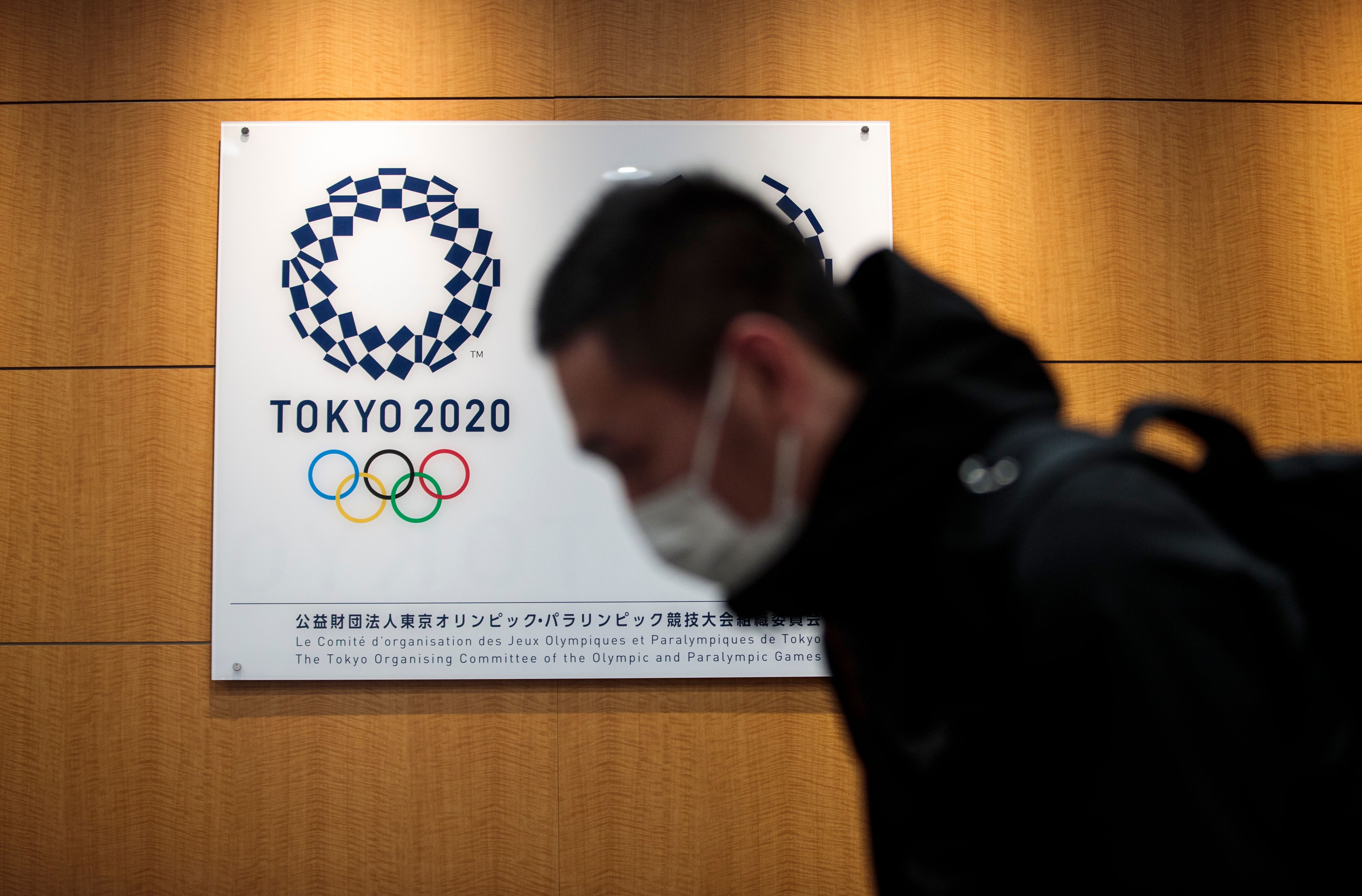A reporter walks past a logo of the Tokyo 2020 Olympic Games after a press conference at the Tokyo 2020 headquarters on March 30, 2020.